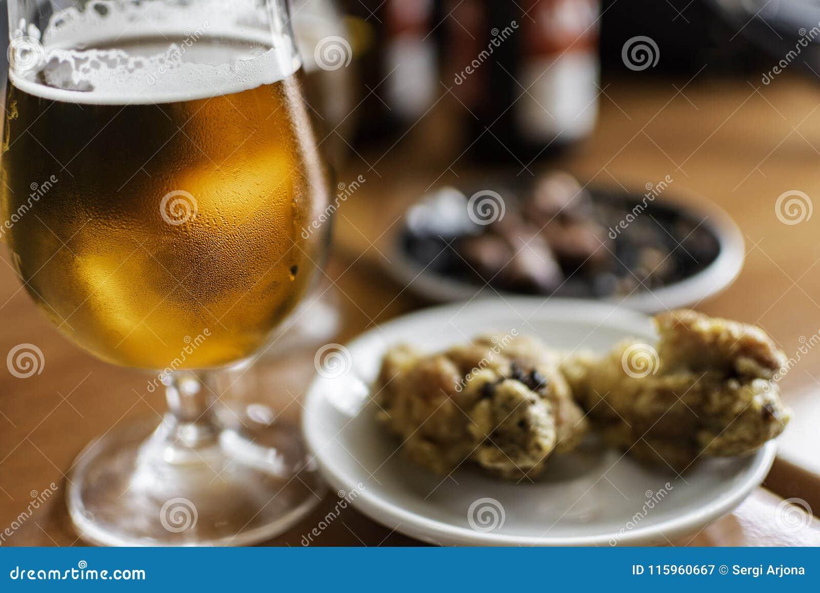 Vidro de cerveja com alimento dos tapas
