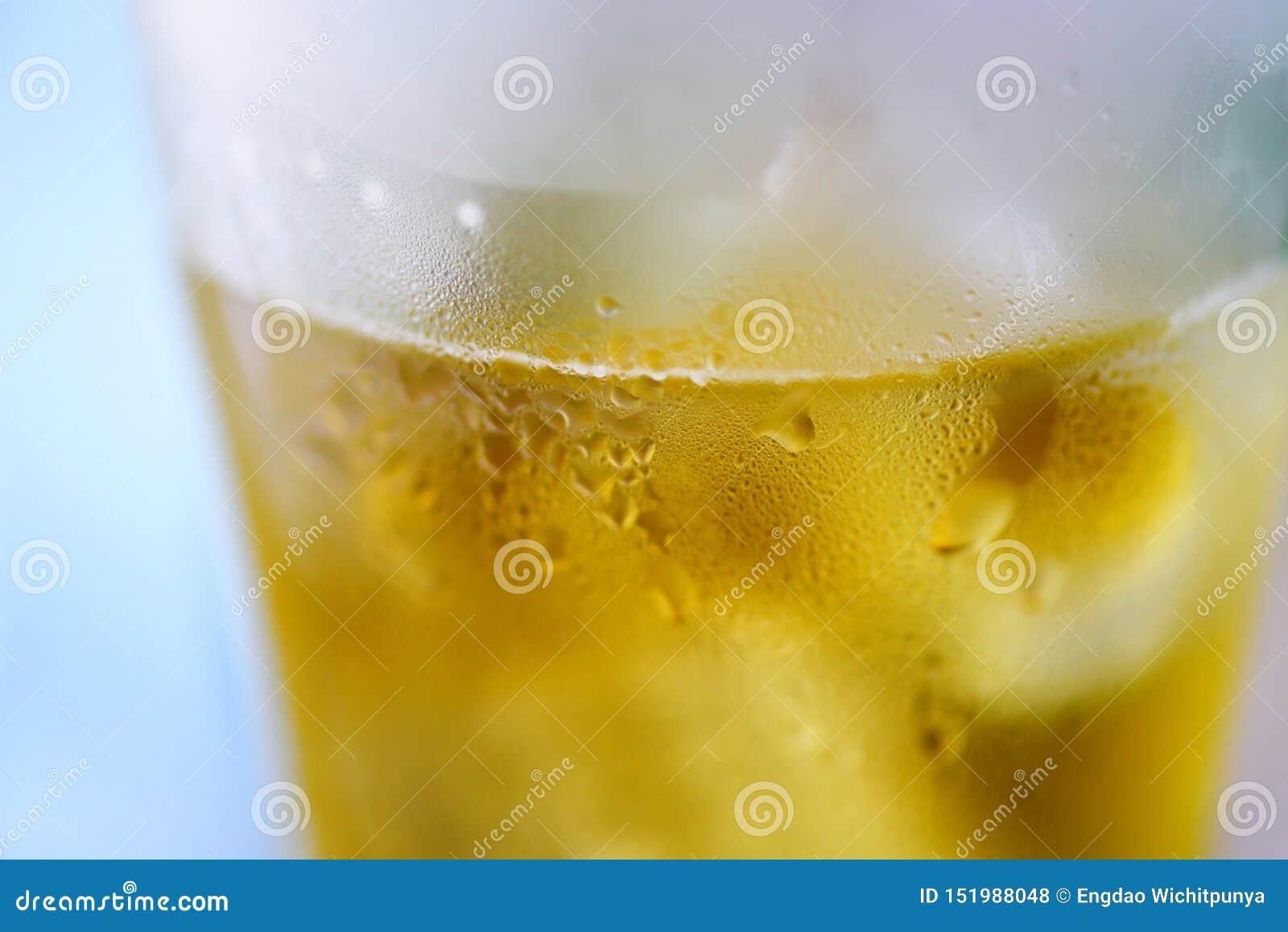 Vidro de cerveja - perto acima da caneca de cerveja das bolhas com gota da água