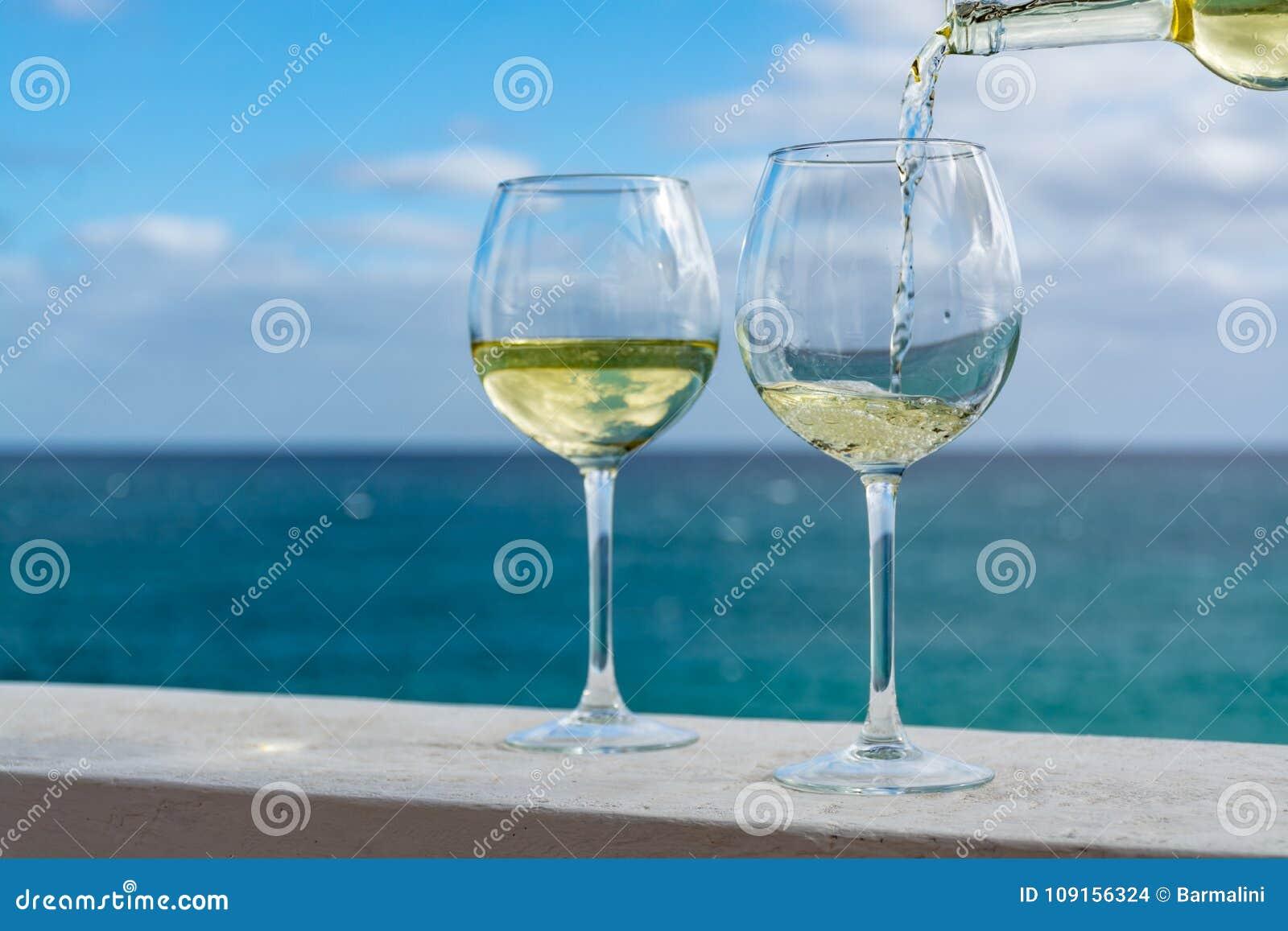Vidro de derramamento do garçom do vinho branco no terraço exterior com mar v