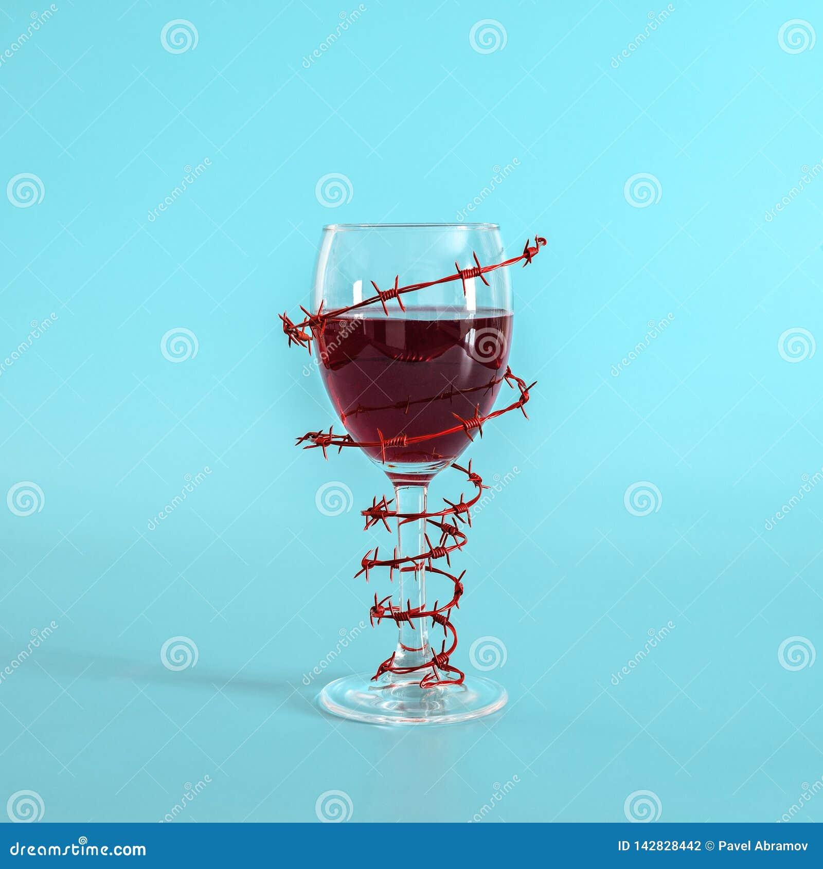 Vidro de vinho com o vinho tinto envolvido com arame farpado no fundo azul O conceito do perigo do alcoolismo, apego, recusa de