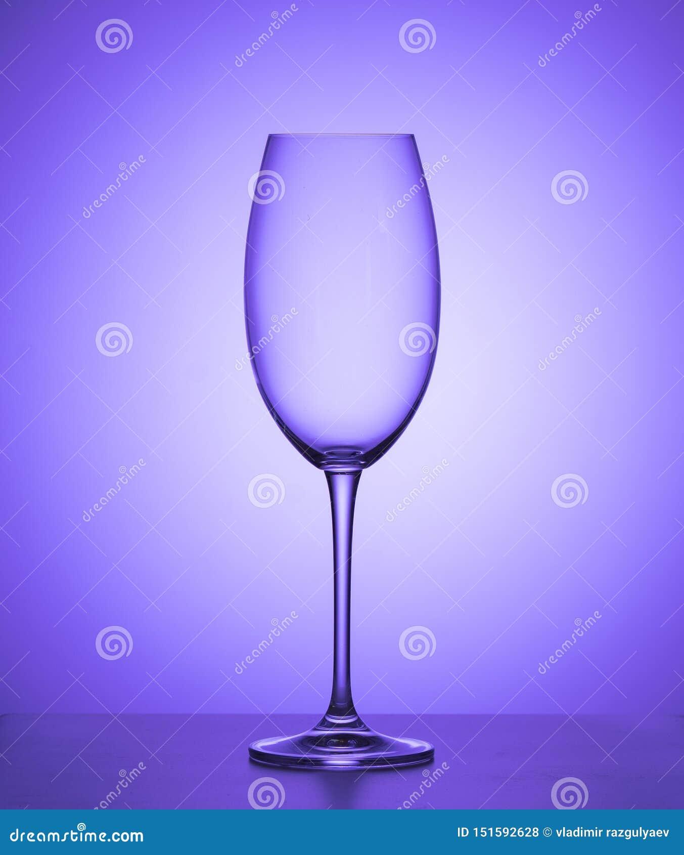 Vidro de vinho vazio em um fundo roxo Fim acima