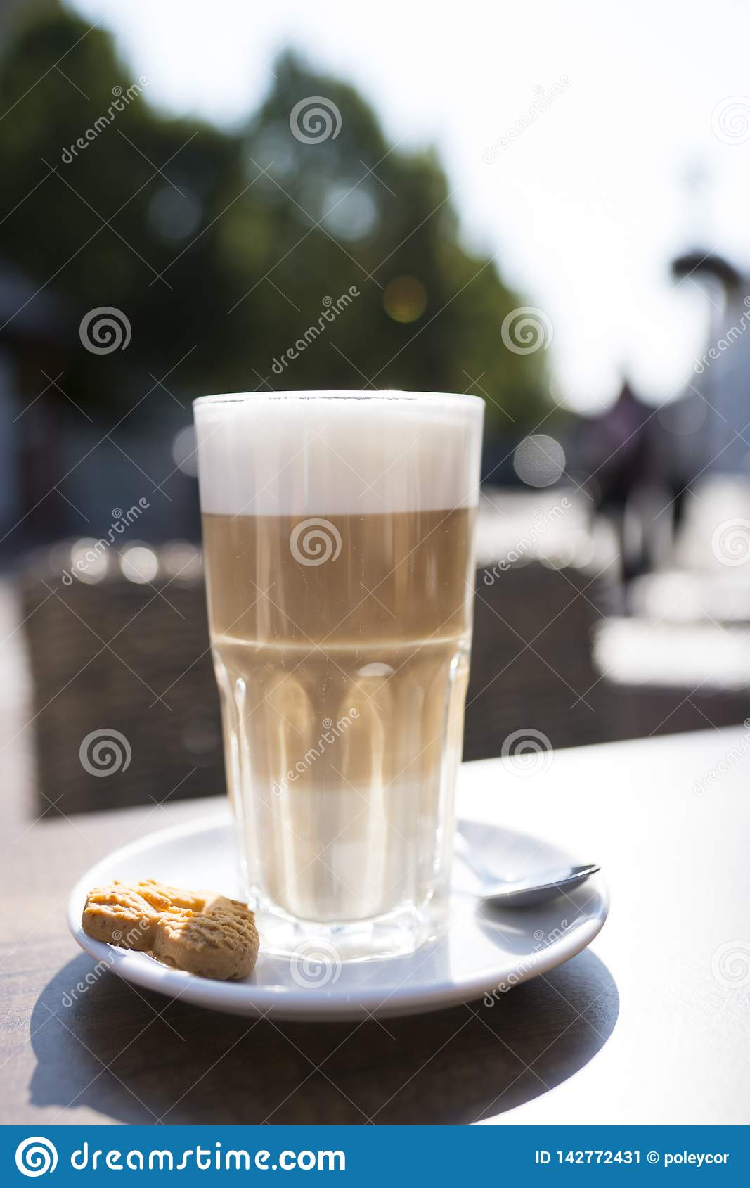 Vidro do macchiato do latte com spume, colher e cookie