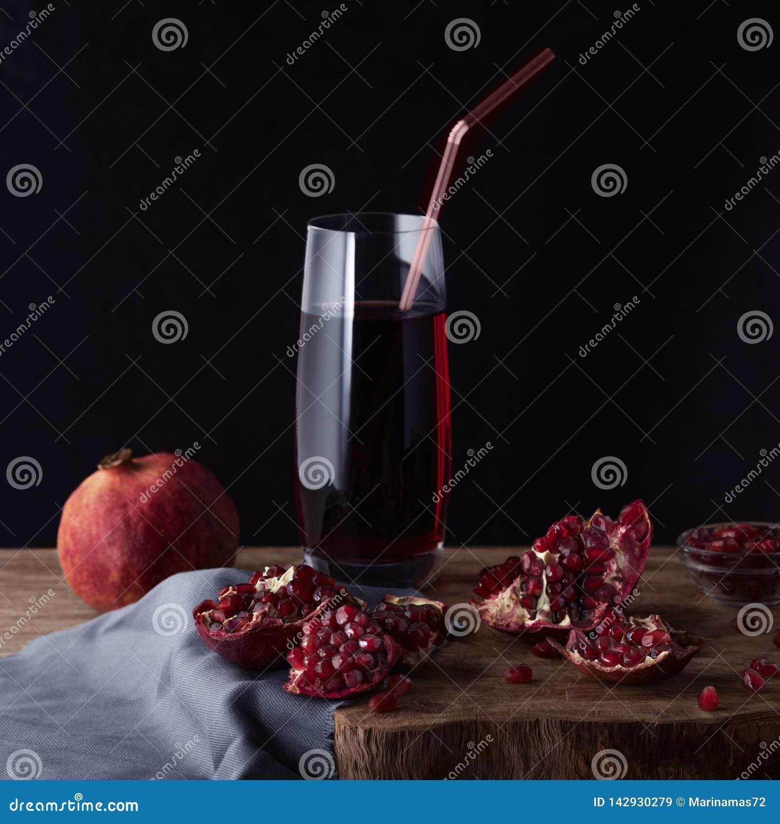 Vidro do suco da romã com fatias da romã e fruto da grandada