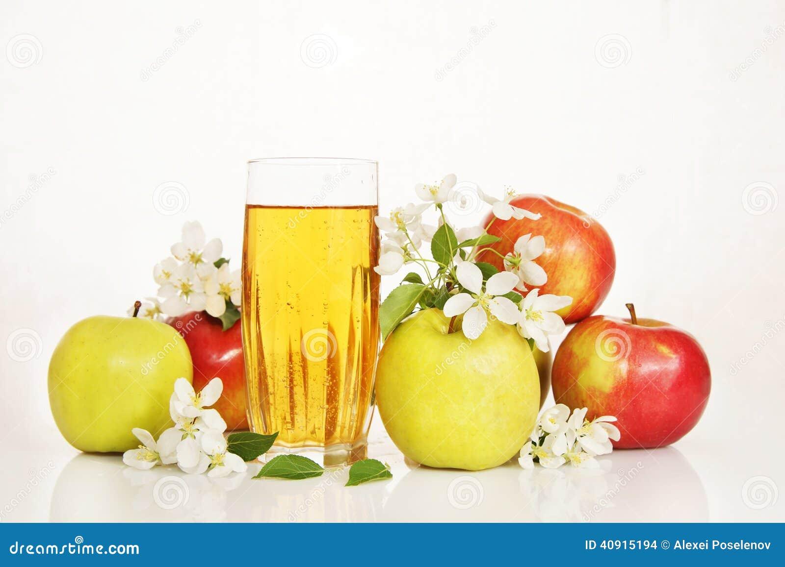 Vidro do suco de maçã fresco com as flores maduras do maçã e as brancas
