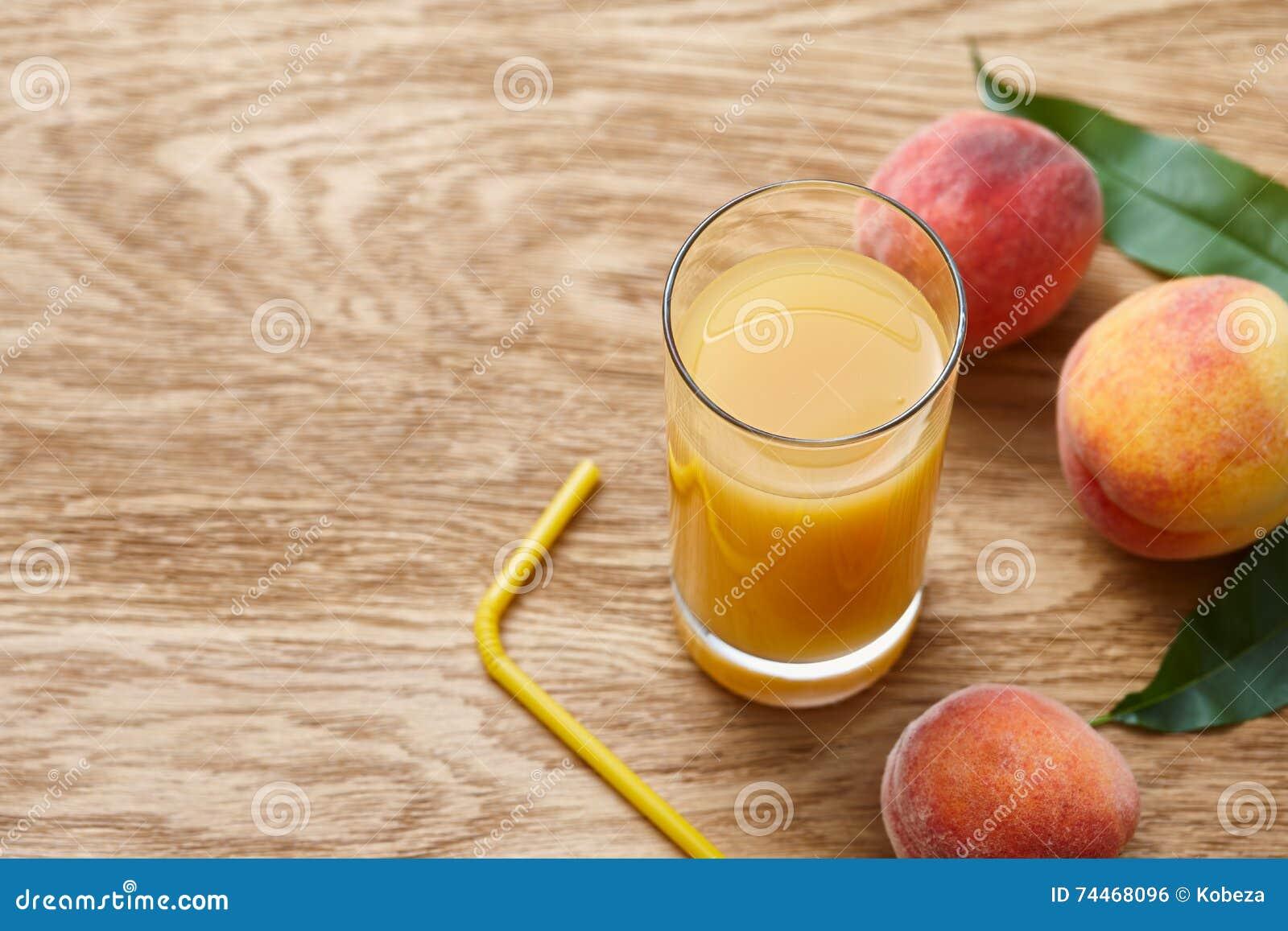 Vidro do suco fresco do pêssego e de frutos maduros