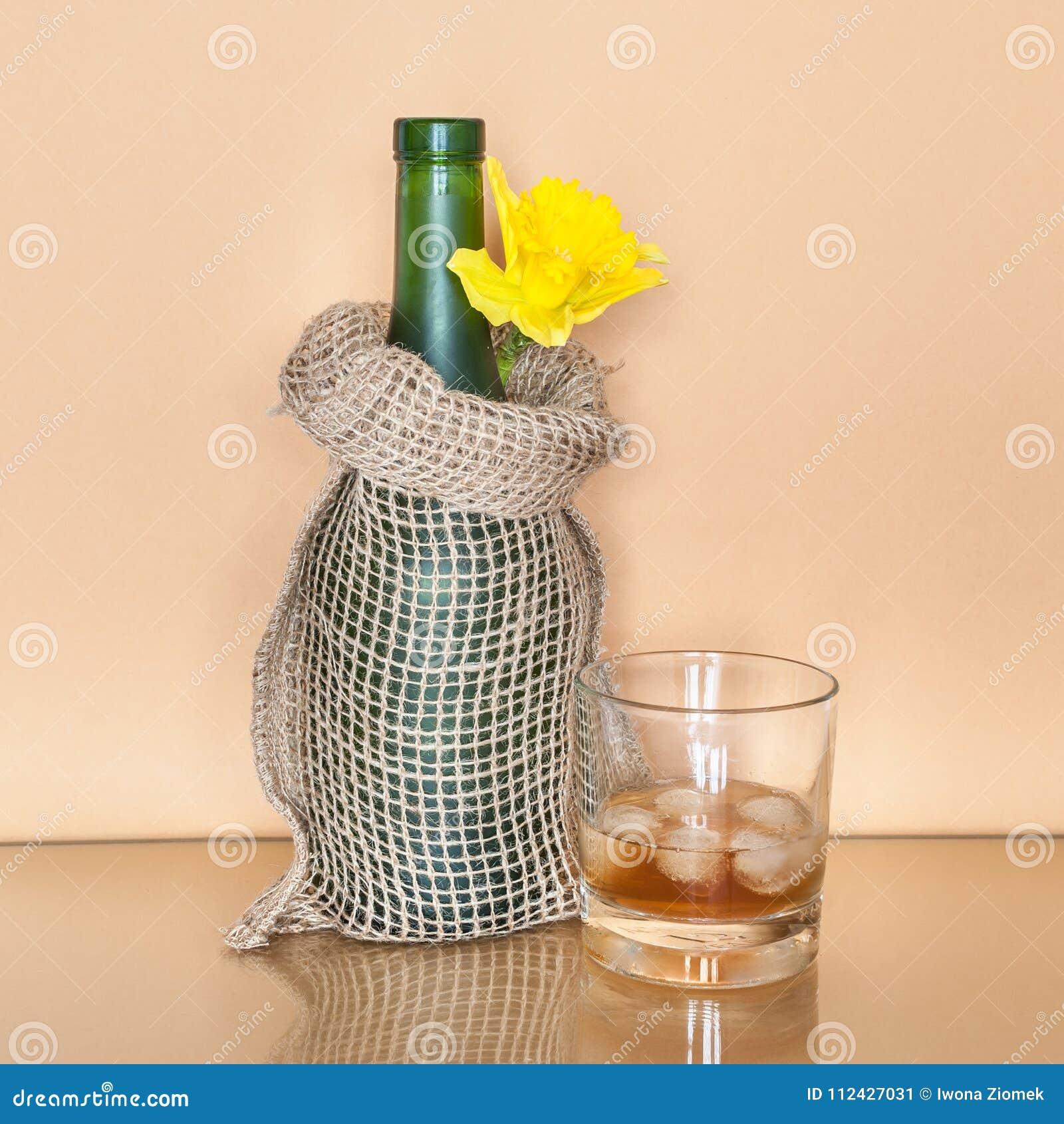 Vidro do uísque com gelo e de uma garrafa envolvida no saco decorativo da lona