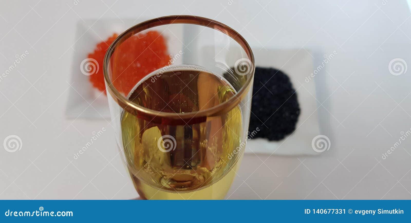 Vidro do vinho espumante branco contra o caviar preto e vermelho