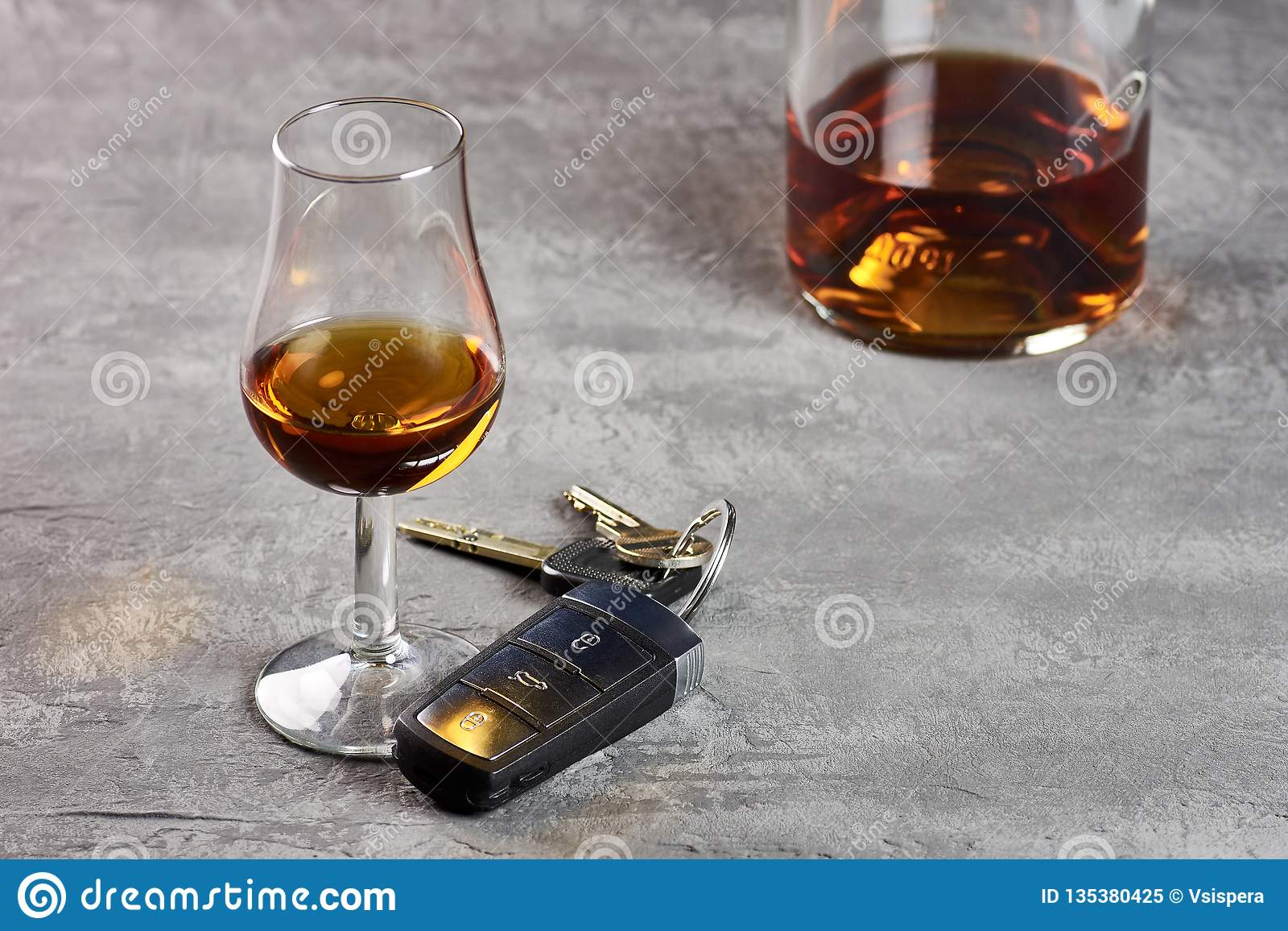 Vidro e garrafa do uísque em um tampo da mesa de pedra e em chaves do carro Condução na embriaguez