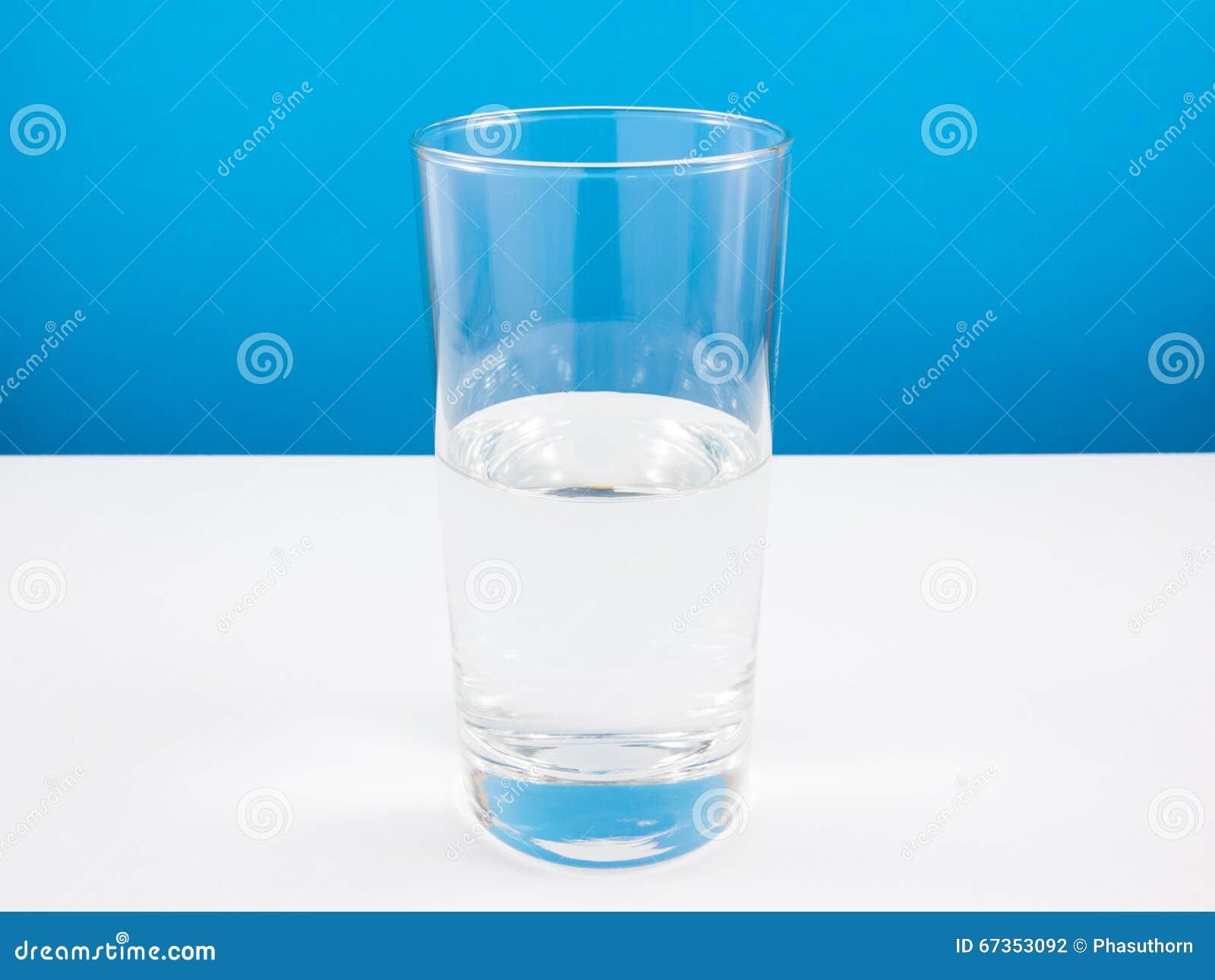 Vidro meio vazio ou meio cheio da água na tabela branca (Para o pensamento do positivo)
