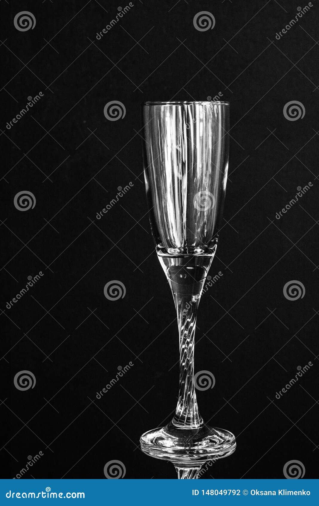 Vidro transparente do champanhe vazio no fundo preto
