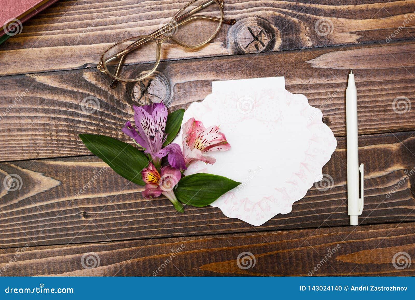 Vidros, caderno e flores no fundo de madeira