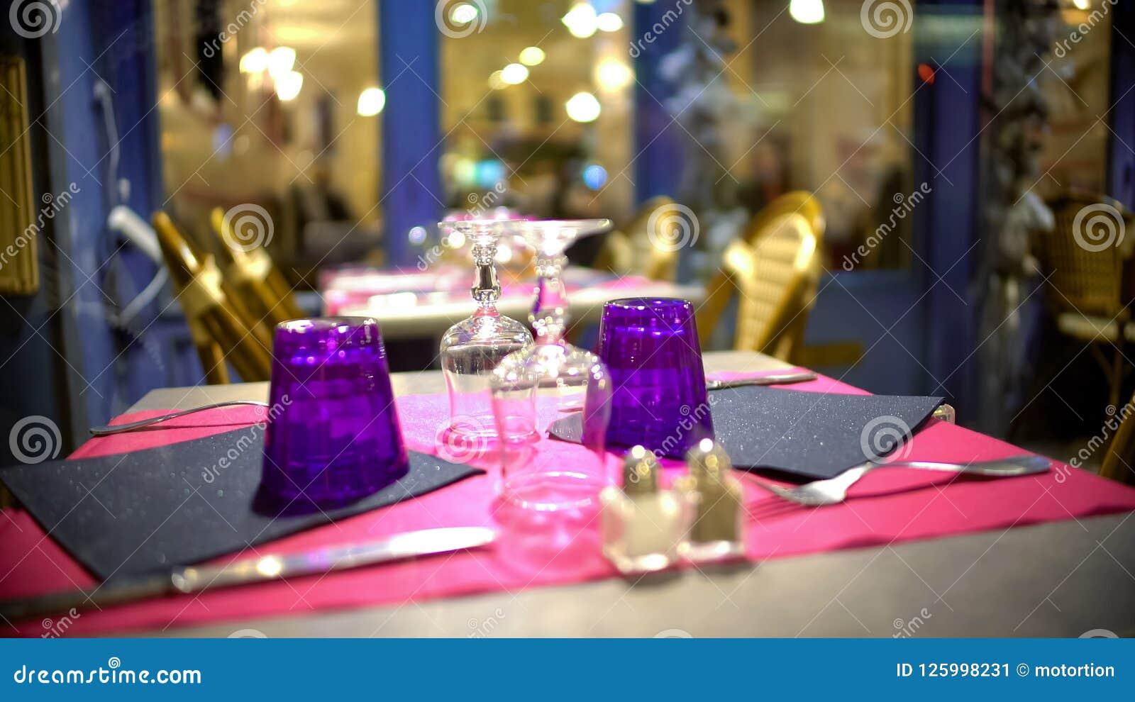 Vidros de cabeça para baixo na tabela fashionably servida no restaurante moderno, close up