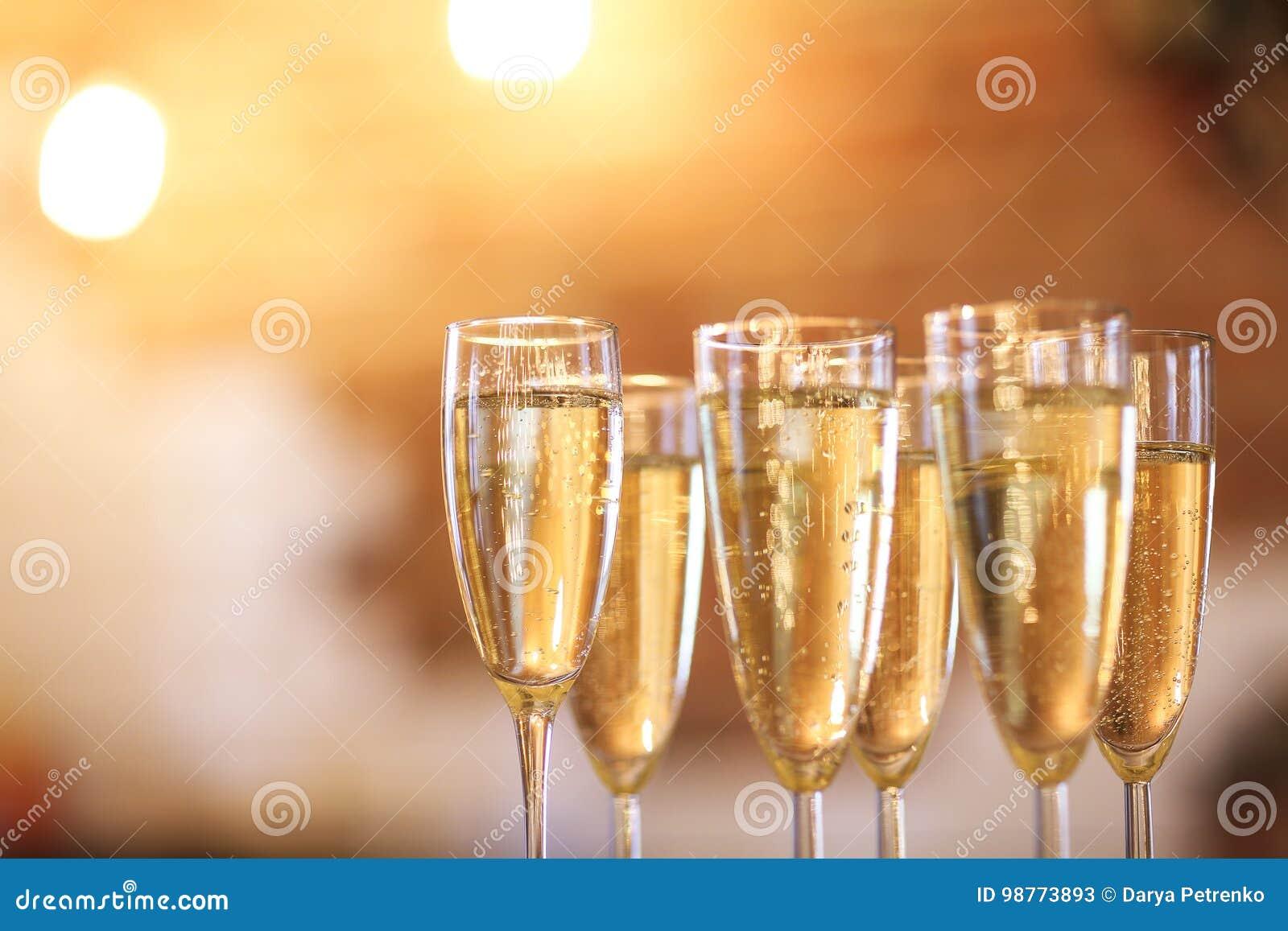 Vidros de Champagne no fundo do ouro Conceito do partido