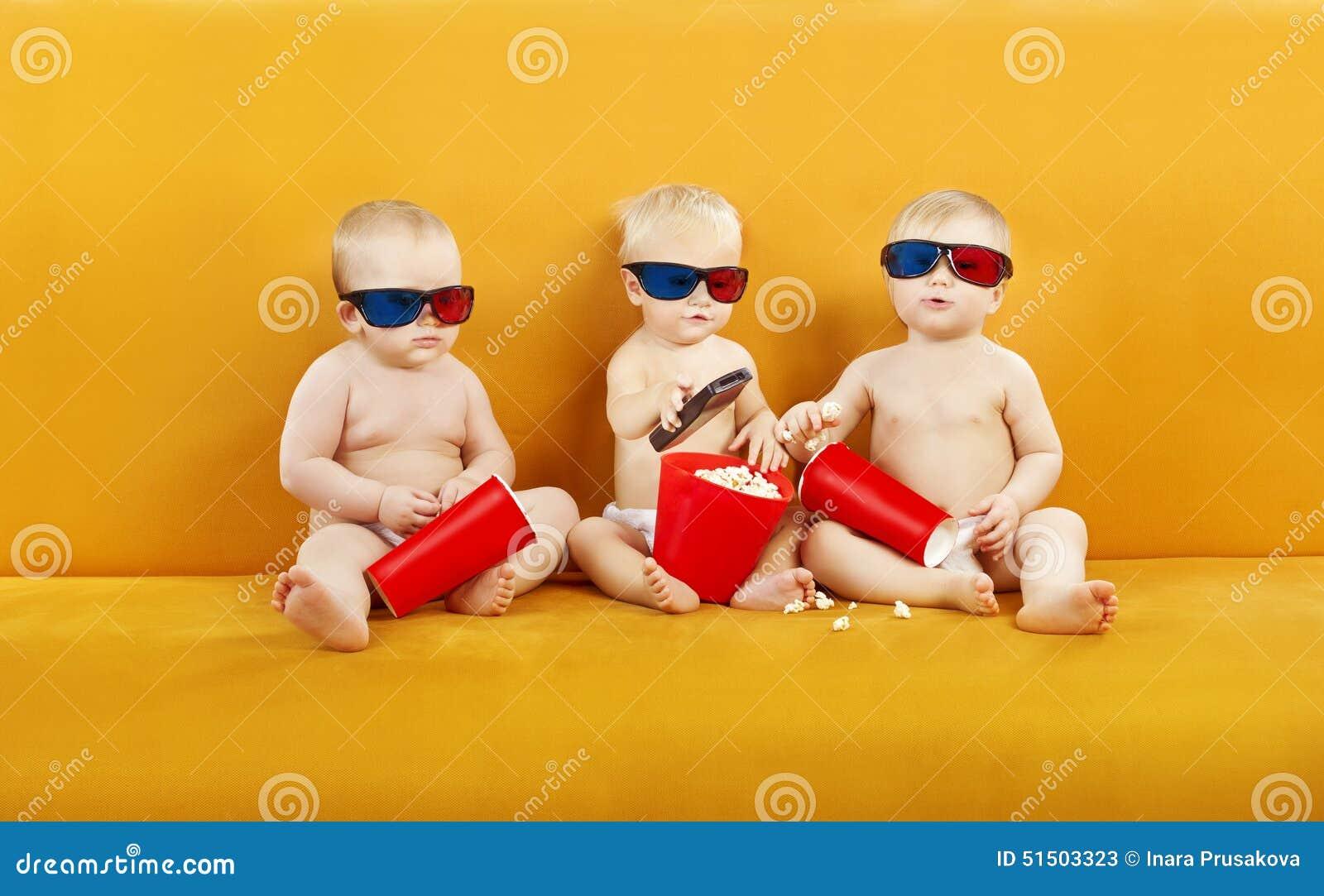 Vidros do bebê 3D que olham o filme na tevê, crianças que comem a pipoca e