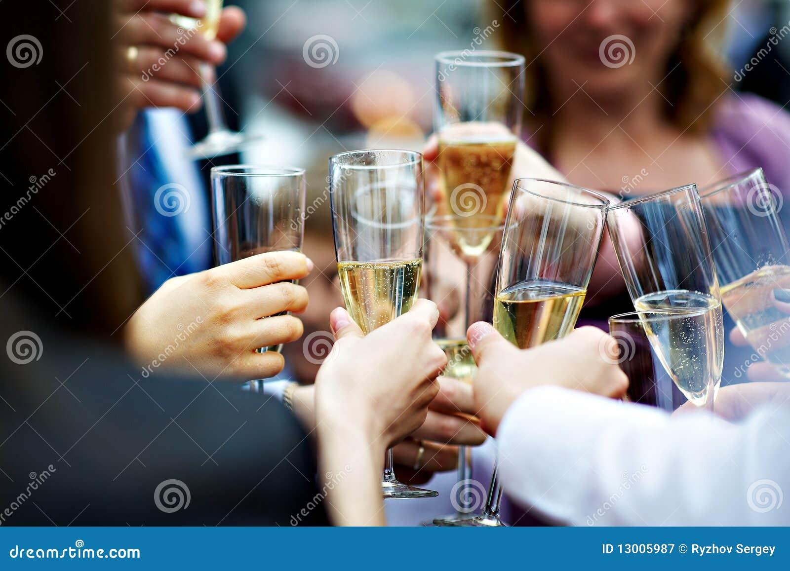 Vidros do champanhe nas mãos dos convidados no casamento