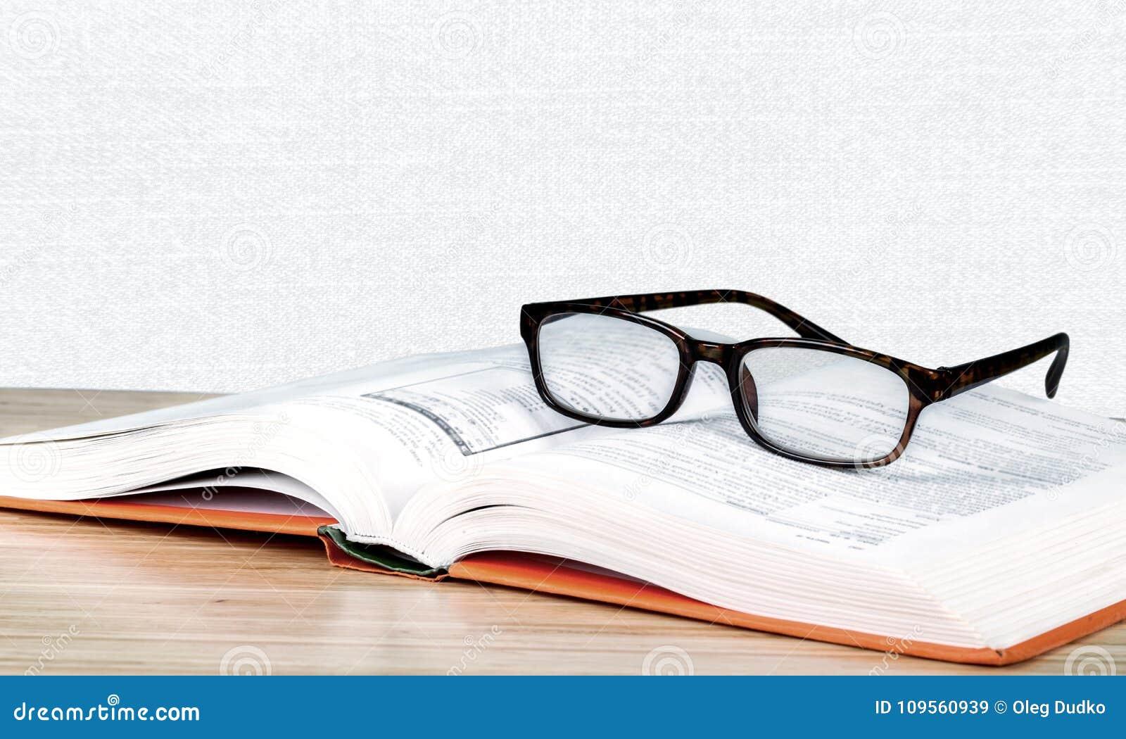 Vidros e livro pretos de leitura do close-up no borrado