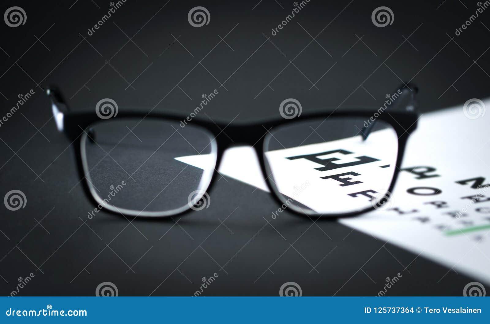 Vidros na carta da letra do teste do olho na tabela do ótico