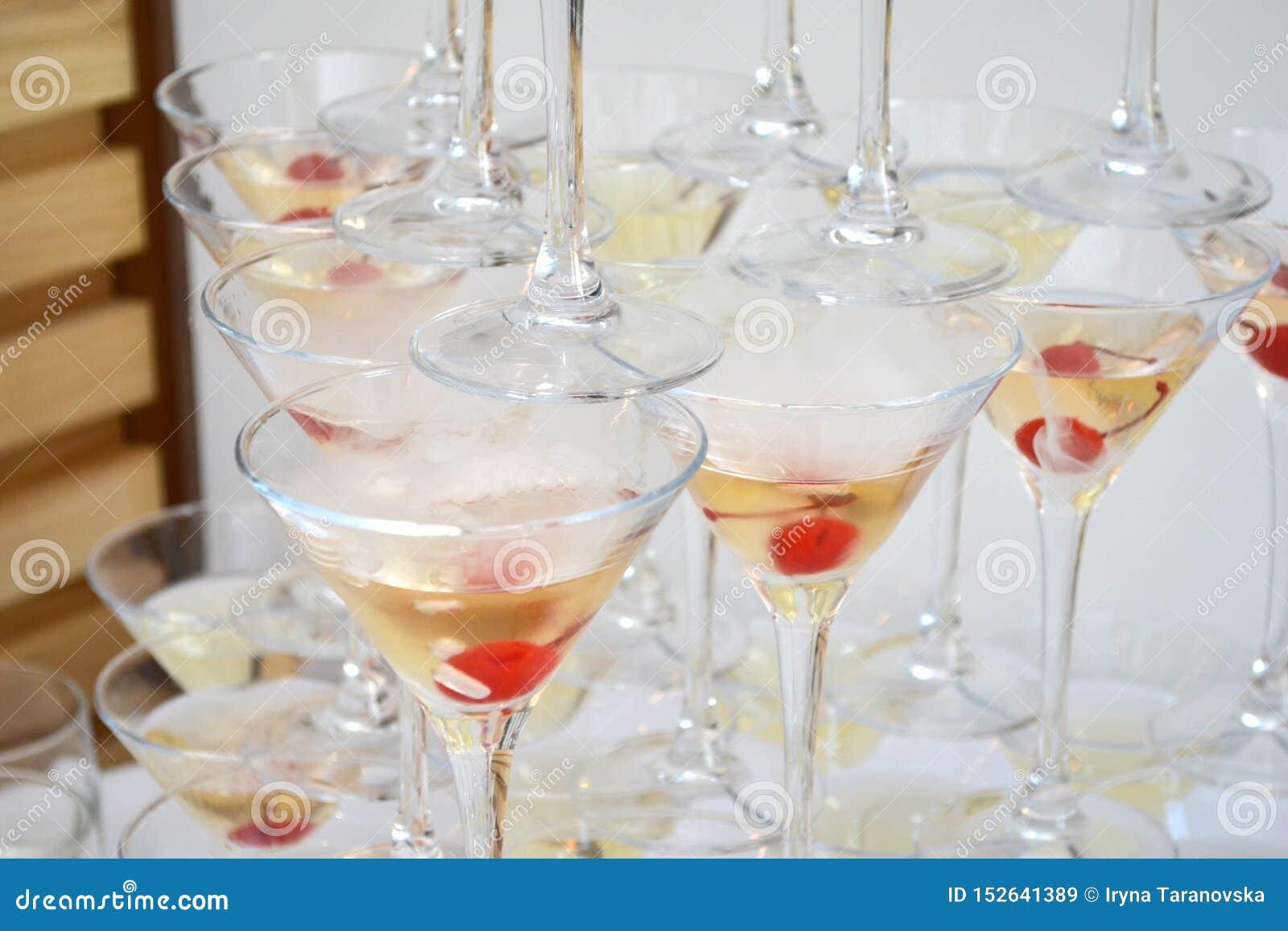 Vidros triangulares de martini, enchidos com o champanhe com as cerejas e o nitrogênio líquido, criando o vapor, forma de uma pir