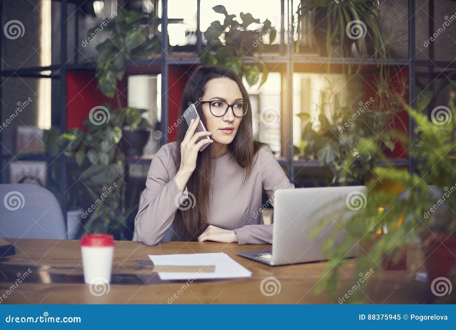 Vidros vestindo do olho da menina bonita no estúdio coworking que fala pelo smartphone Conceito dos jovens que trabalham com disp