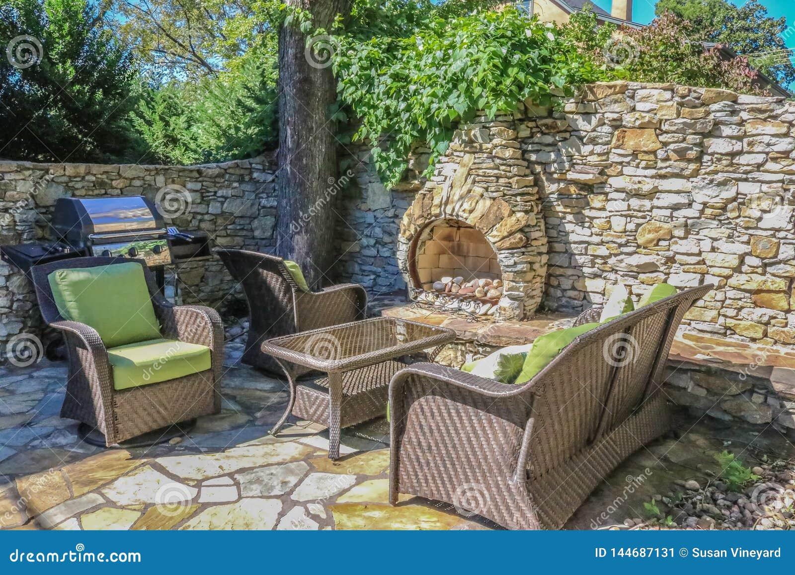Vie extérieure - mur de roche et cheminée extérieure intégrée construits autour d un arbre faisant le coin avec des meubles