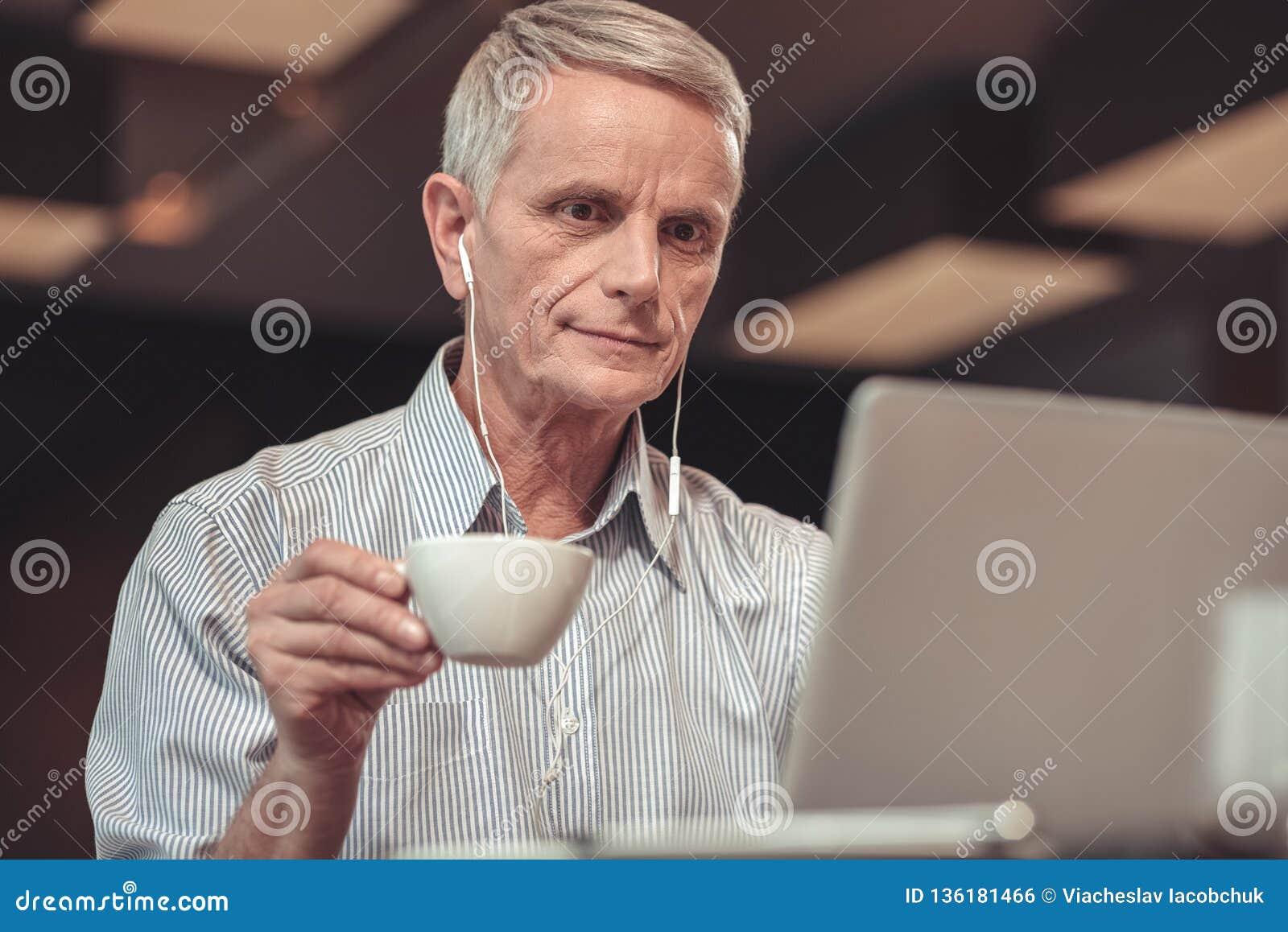 Vieil homme attentif écoutant la musique dans un restaurant