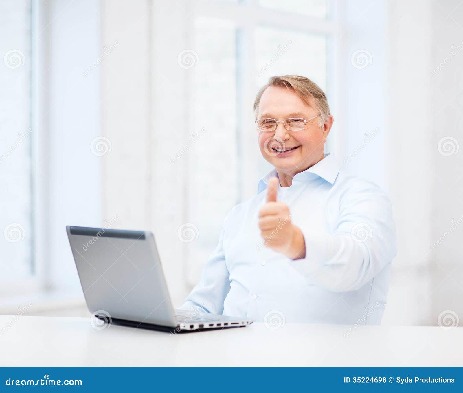 vieil homme avec l 39 ordinateur portable montrant des pouces photo stock image du laptop gentil. Black Bedroom Furniture Sets. Home Design Ideas