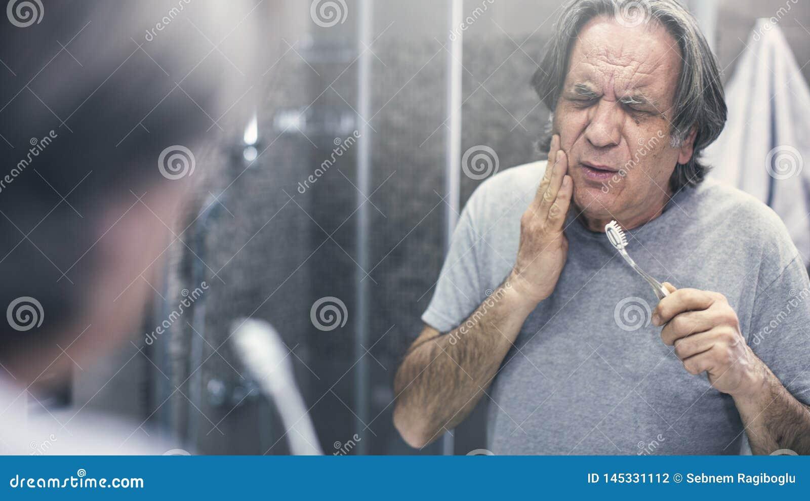 Vieil homme avec le mal de dents devant le miroir