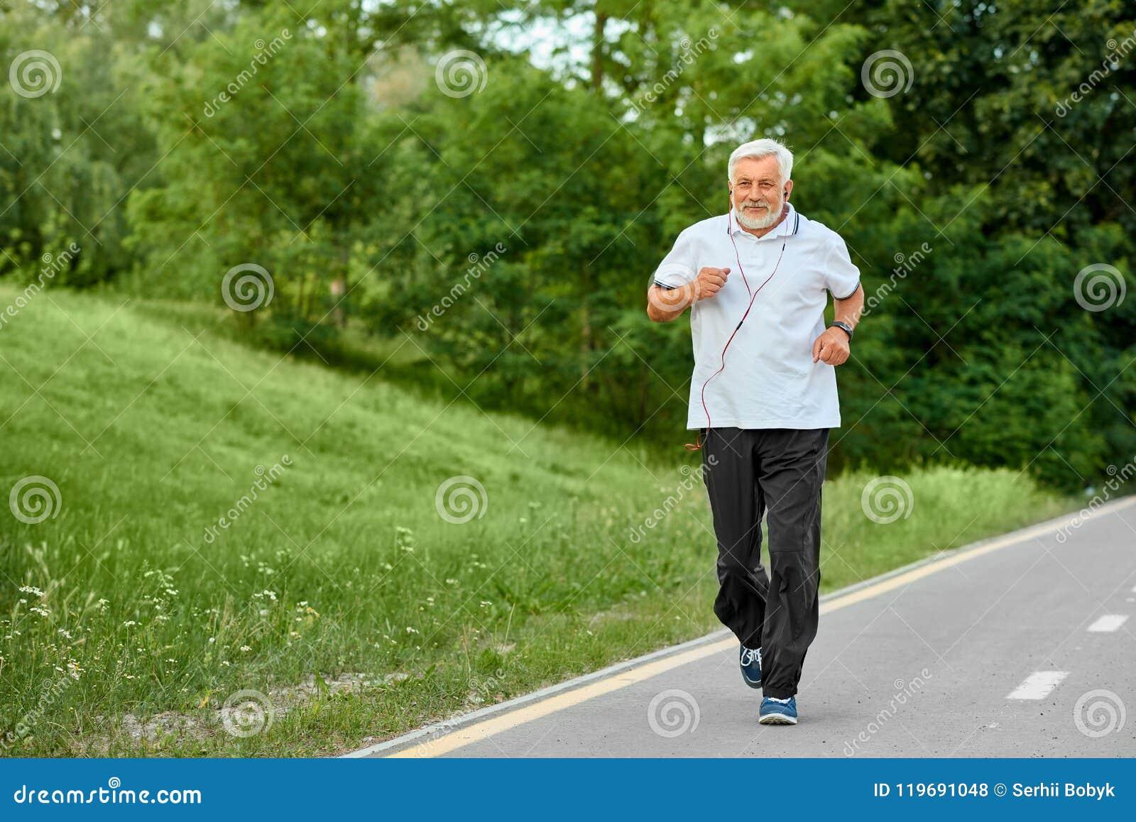Vieil homme convenable courant sur le champ de courses en parc vert