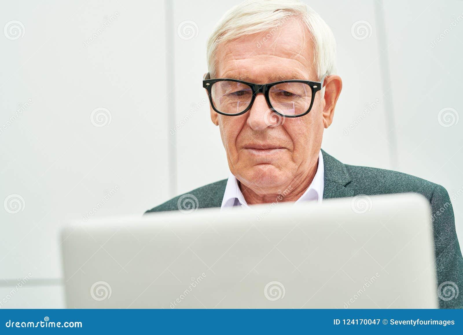 Vieil homme d affaires avec l ordinateur portatif