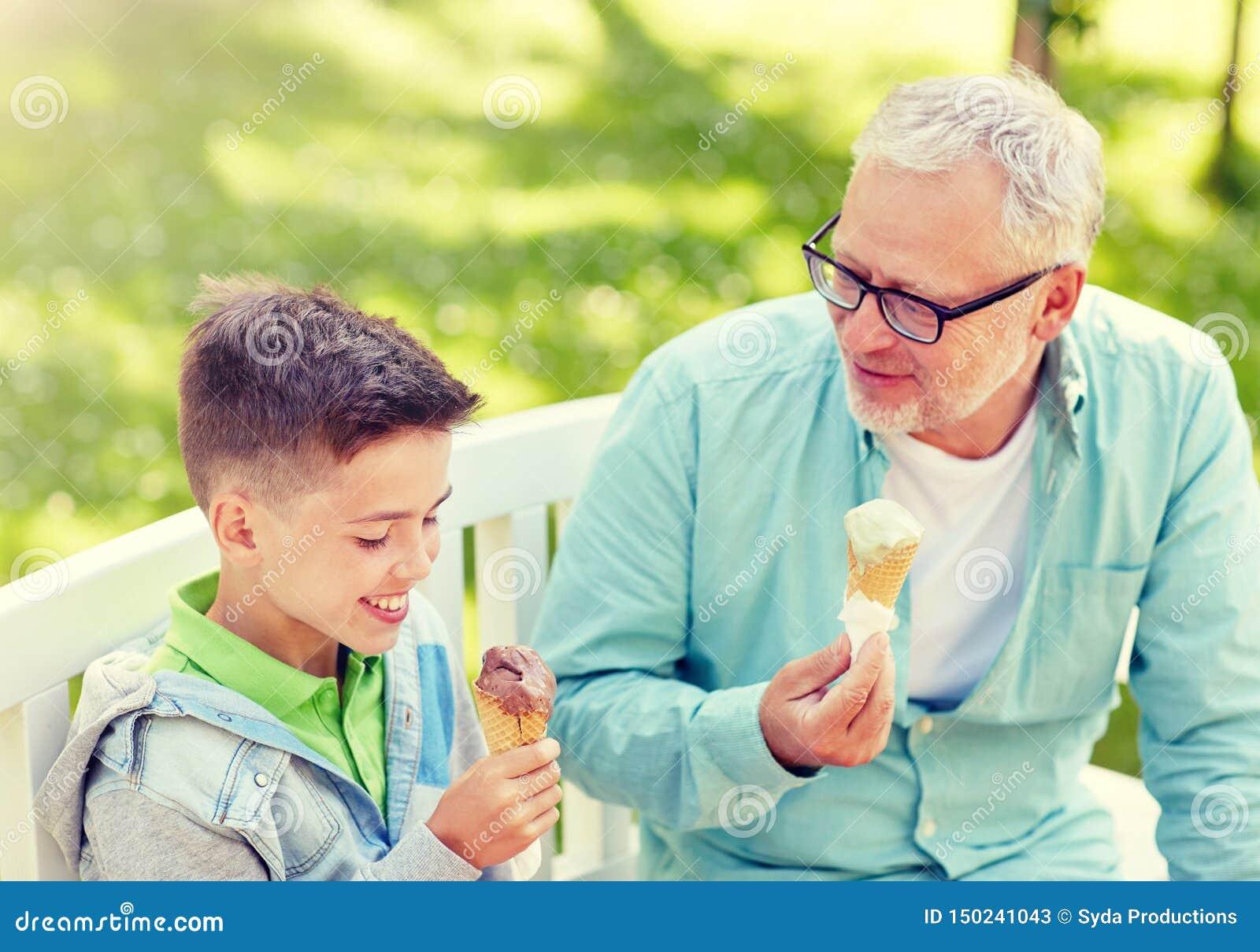Vieil homme et gar?on mangeant la cr?me glac?e au parc d ?t?