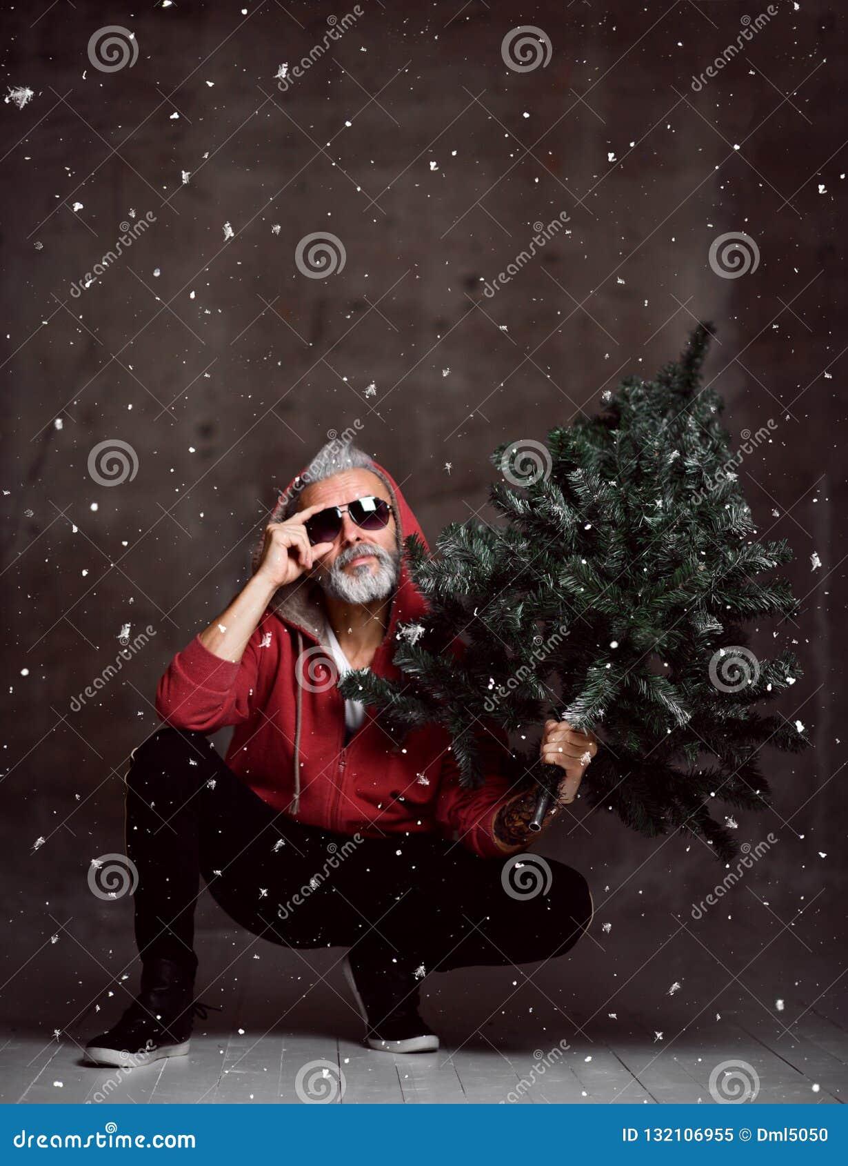 Vieil homme moderne à la mode de Santa dans le hoodie rouge de mode sous le Joyeux Noël de neige
