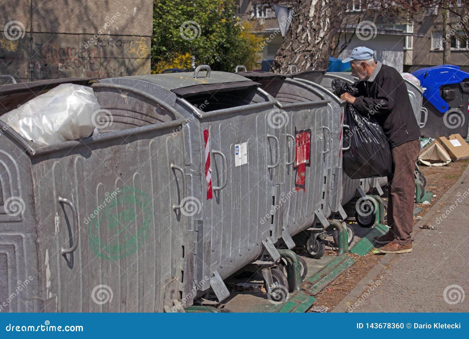 Vieil homme recherchant les bouteilles en plastique dans les décharges, plongée de décharge