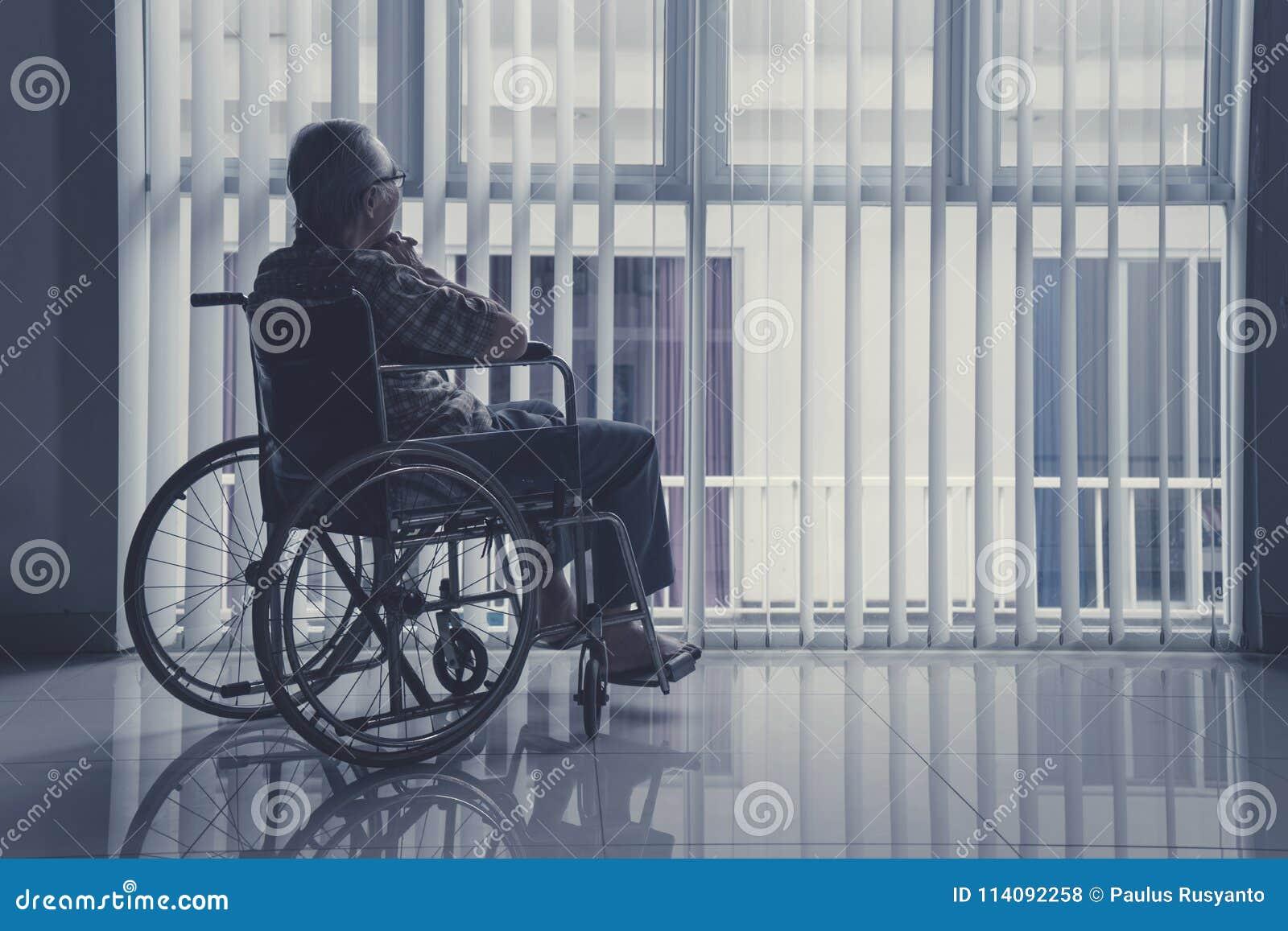 Vieil homme seul s asseyant sur le fauteuil roulant à la maison