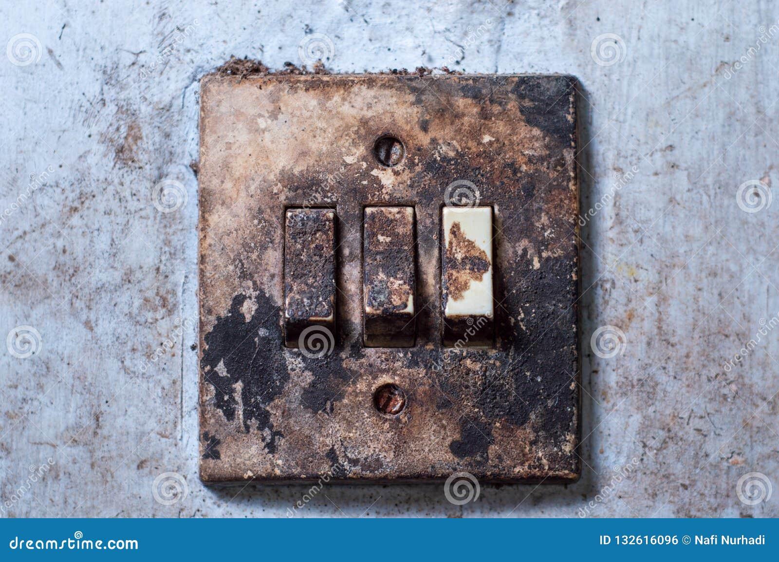 Vieil interrupteur de lampe monté sur un mur blanc