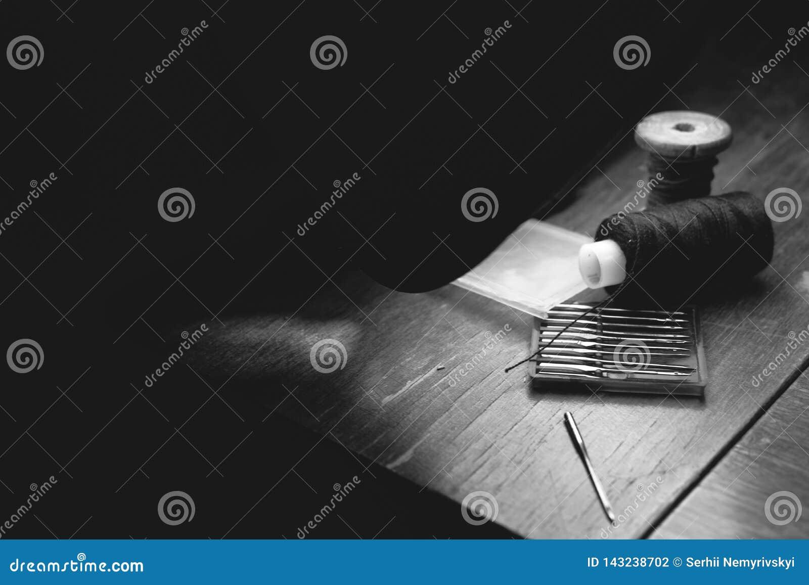 Vieille aiguille de machine à coudre avec le fil noir, sur une vieille table de travail sale Table de travail du ` s de tailleur
