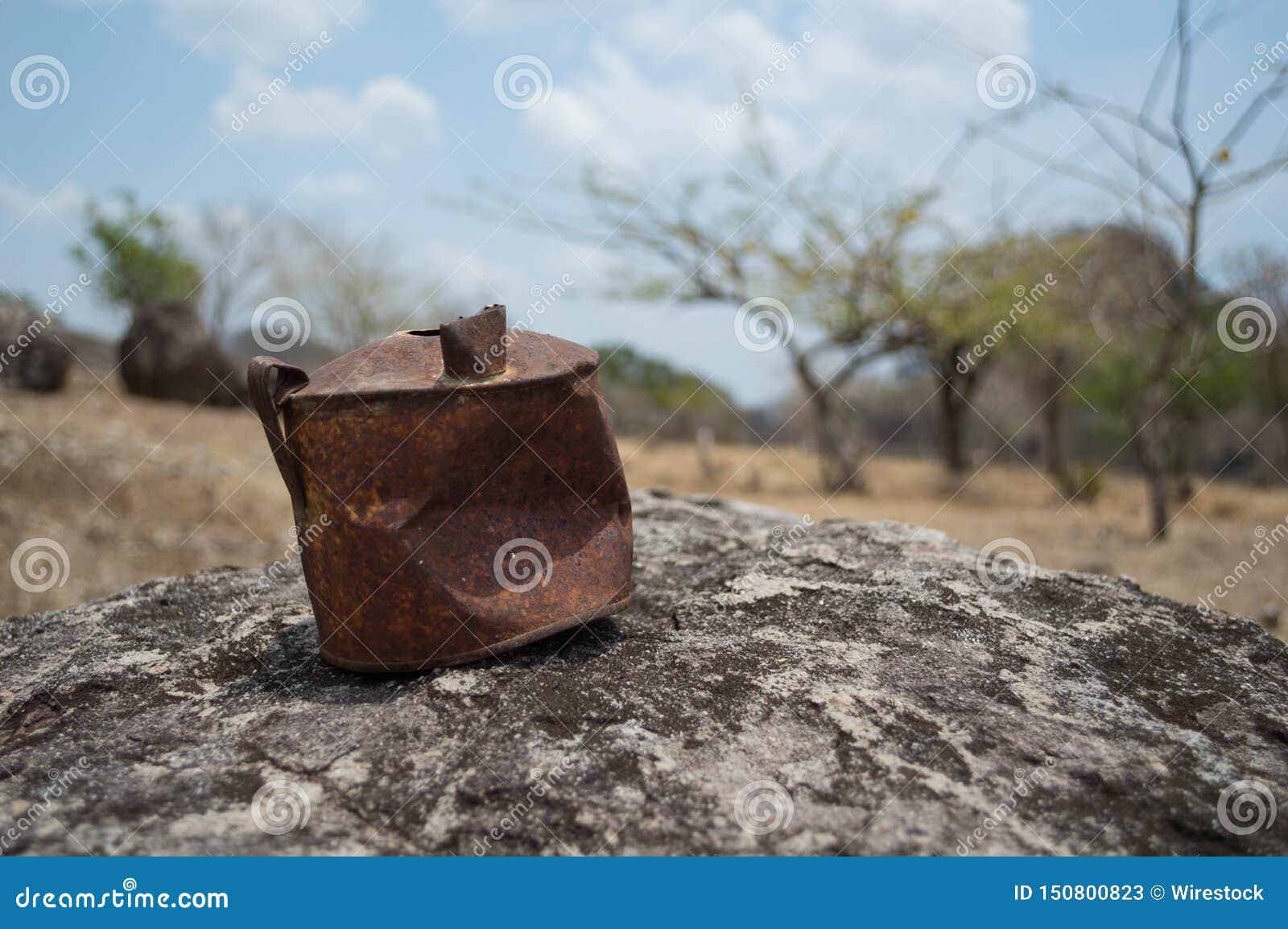 Vieille boîte rouillée sur une roche dans un désert