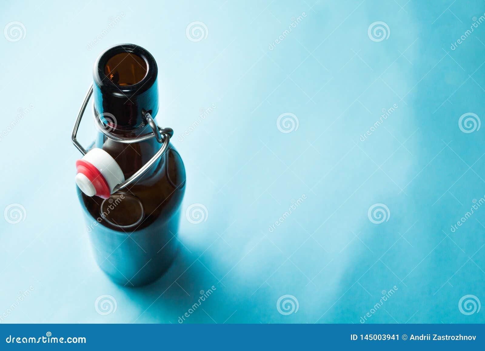 Vieille bouteille brune avec de la bi?re sans label sur un fond bleu L espace pour le texte