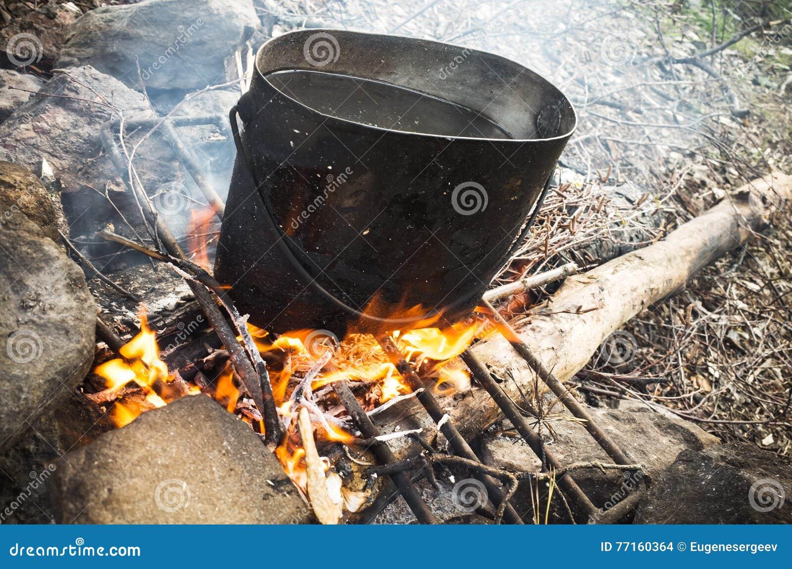 Vieille casserole noire de suie sur un feu