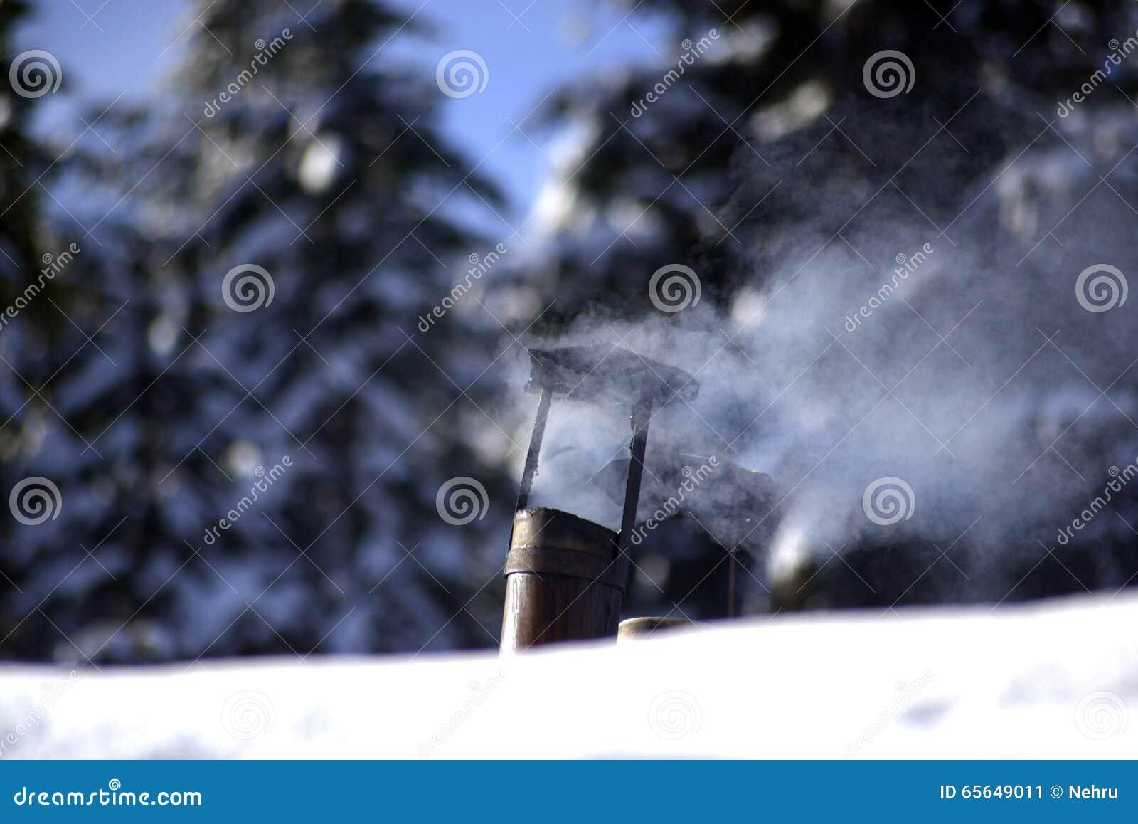 Vieille cheminée de tabagisme de bidon sur un toit neigeux