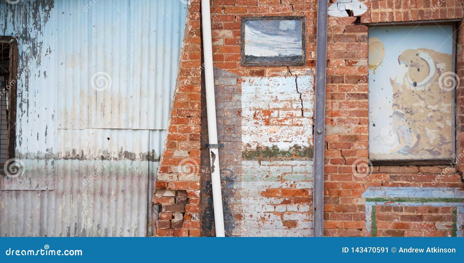 Vieille course en bas du mur fait de briques et fer ondulé