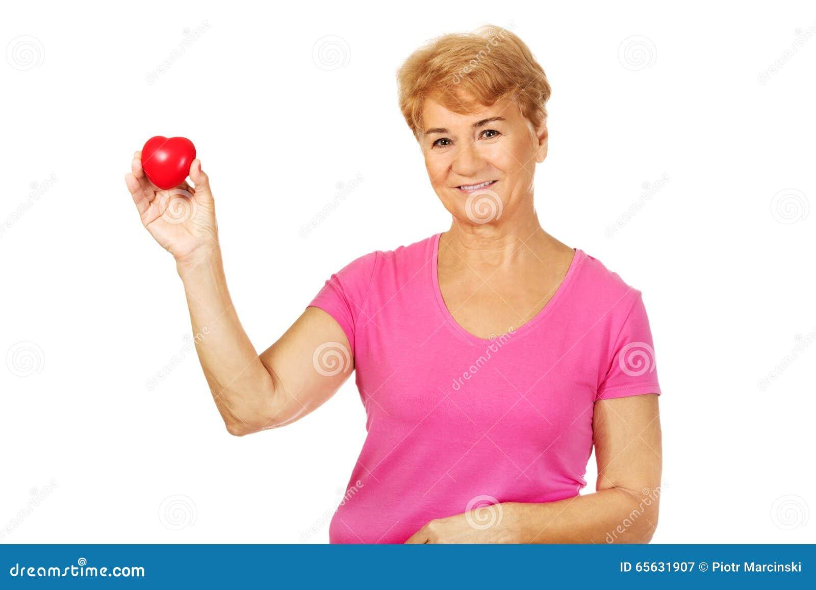 Vieille femme de sourire tenant le coeur rouge de jouet