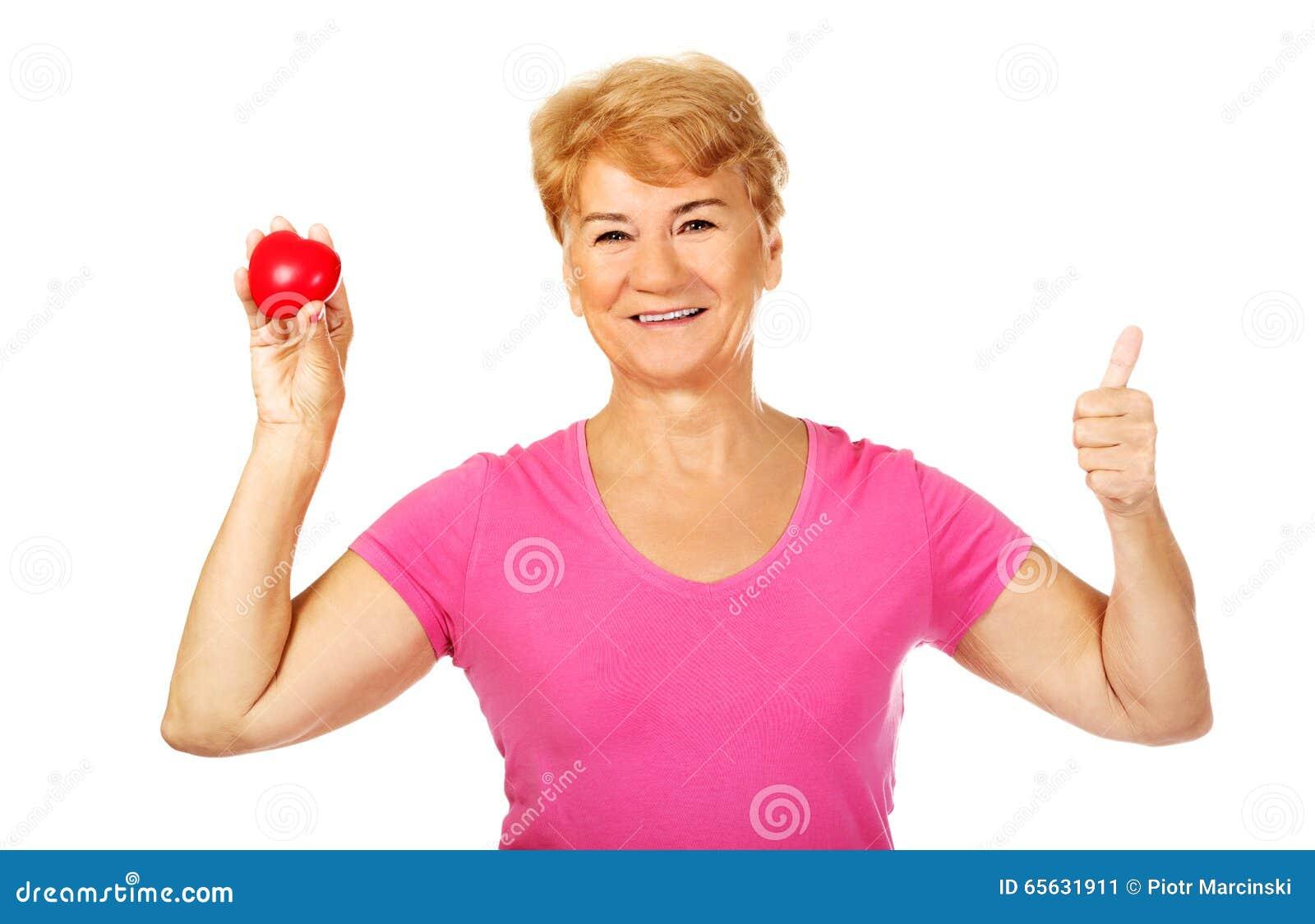 Vieille femme de sourire tenant le coeur rouge de jouet avec le pouce