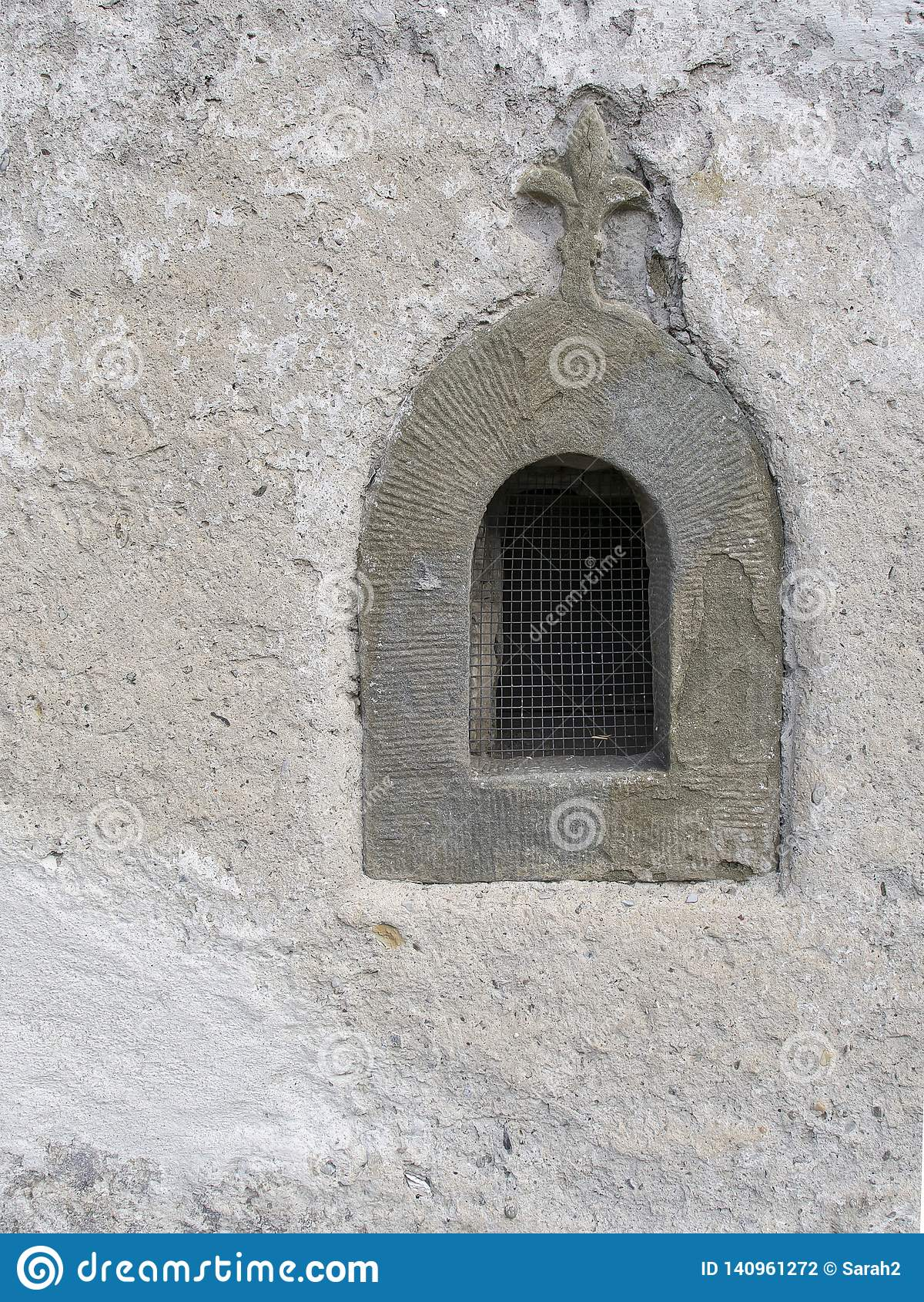 Vieille fenêtre en pierre avec le motif religieux et le gril de fleur de lys