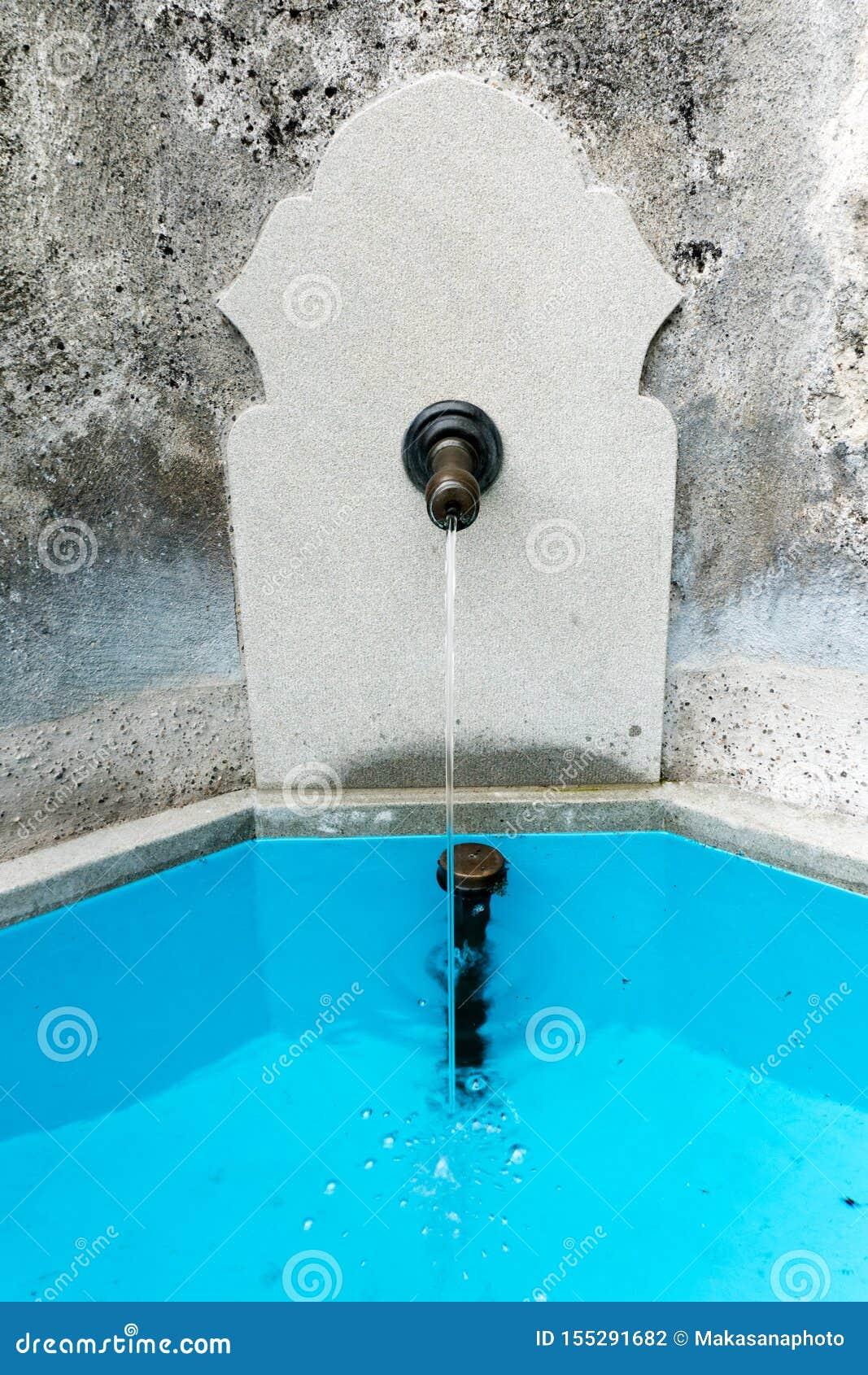 Vieille fontaine en pierre avec de l eau potable et un bassin de bec et de turquoise en métal
