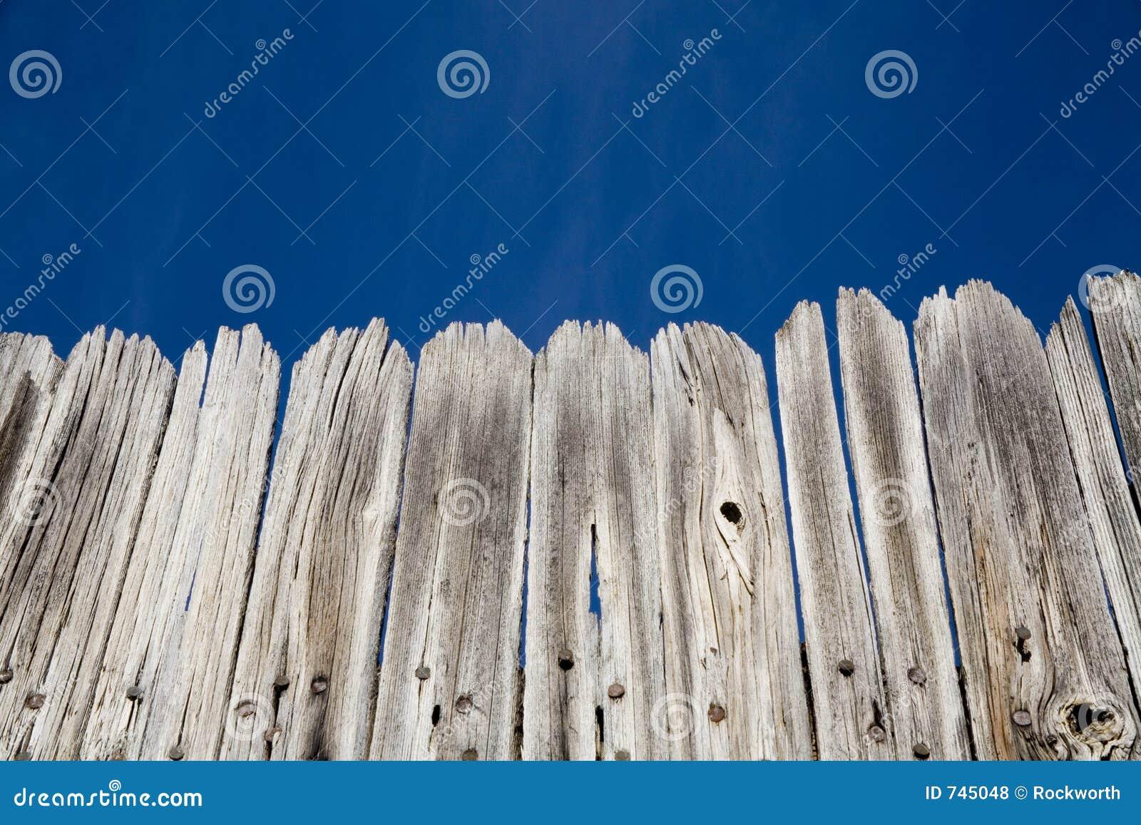 Vieille frontière de sécurité en bois et ciel bleu lumineux