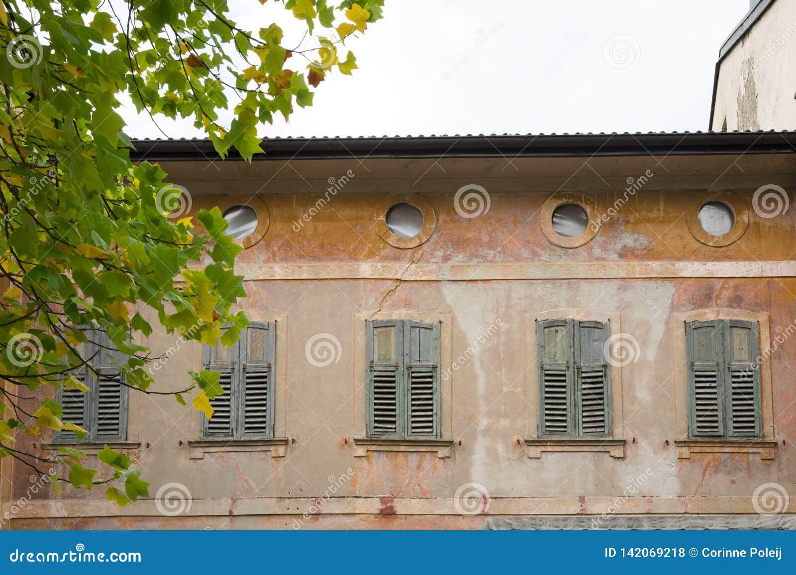 Vieille maison peinte avec des volets dans Levico Termen, Italie