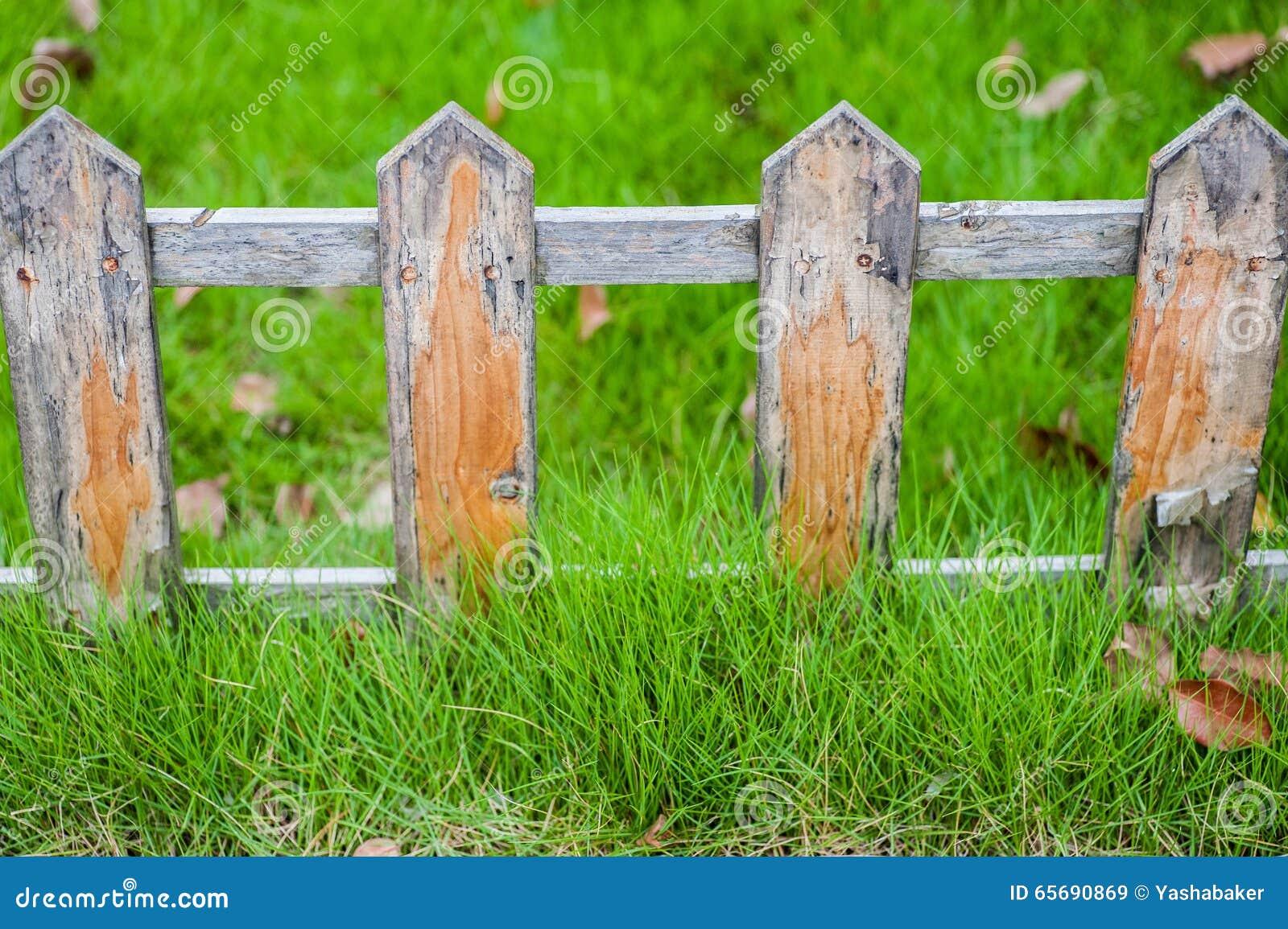 Vieille petite barrière sur la pelouse verte profondément dans l herbe
