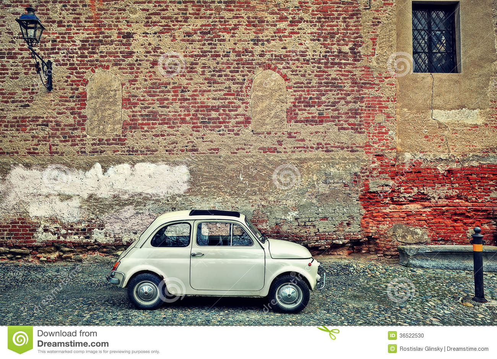 Vieille petite voiture contre le mur de briques.