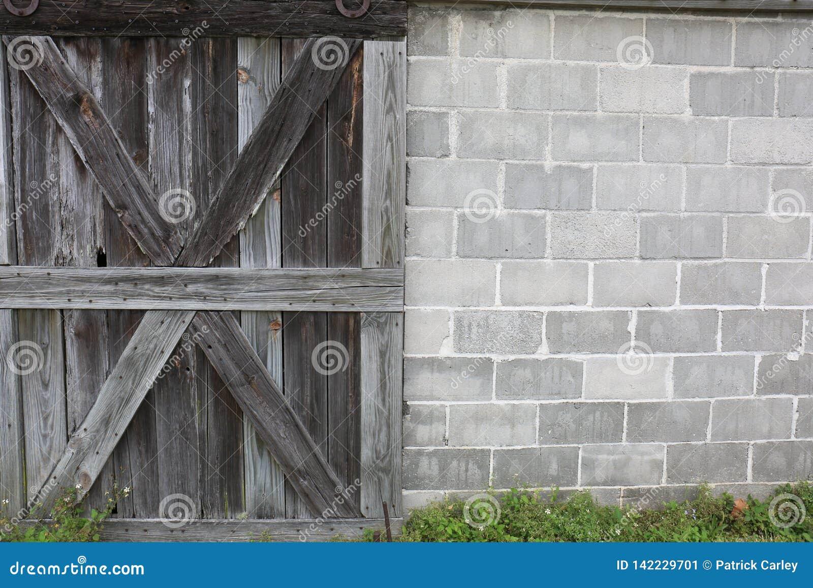 Vieille porte de grange superficielle par les agents en bois avec le mur de bloc de ciment