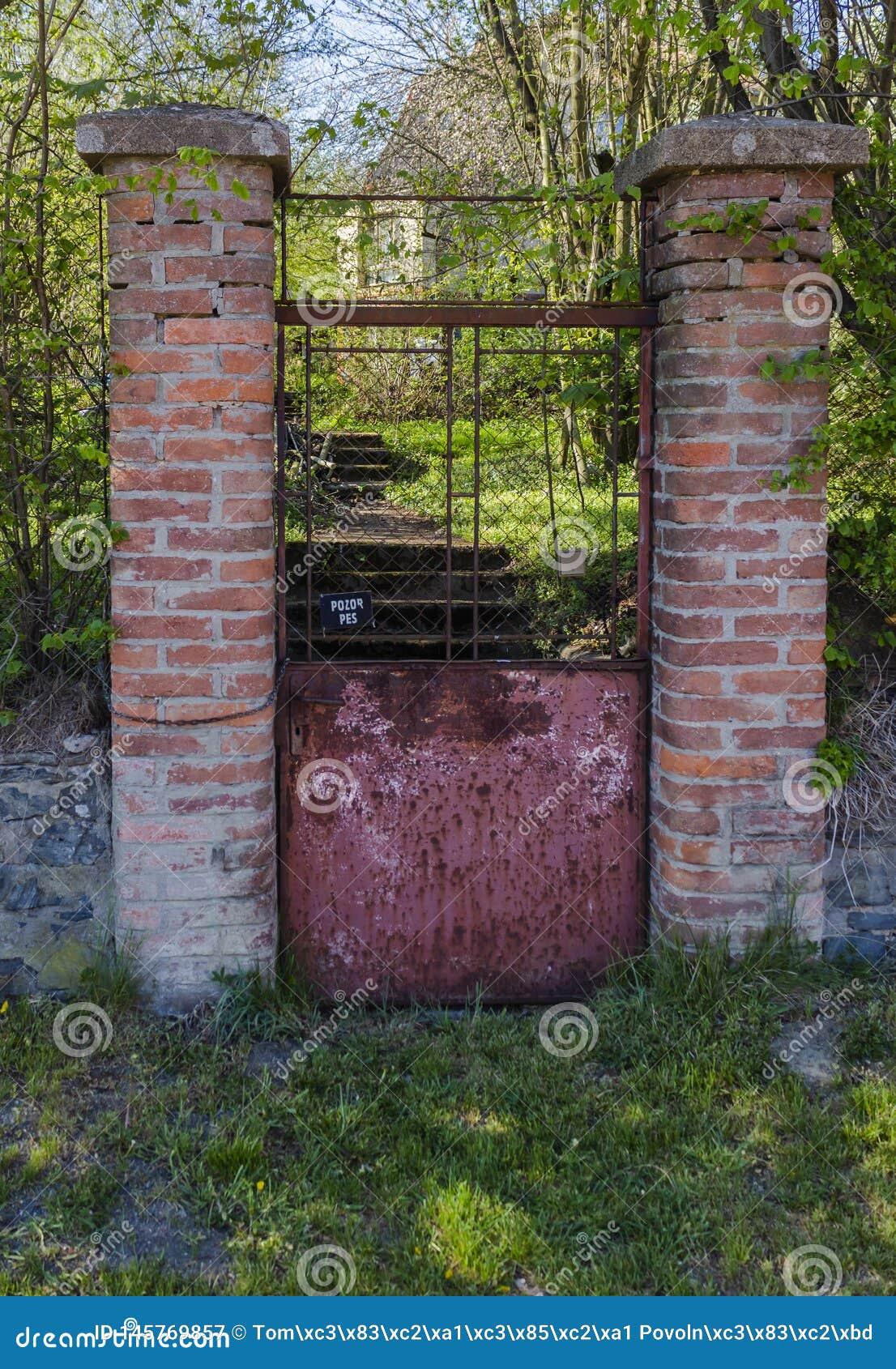 Vieille porte de jardin rouillée superficielle par les agents, avec le signe en Tchèque, qui veut dire : Prenez garde du chien